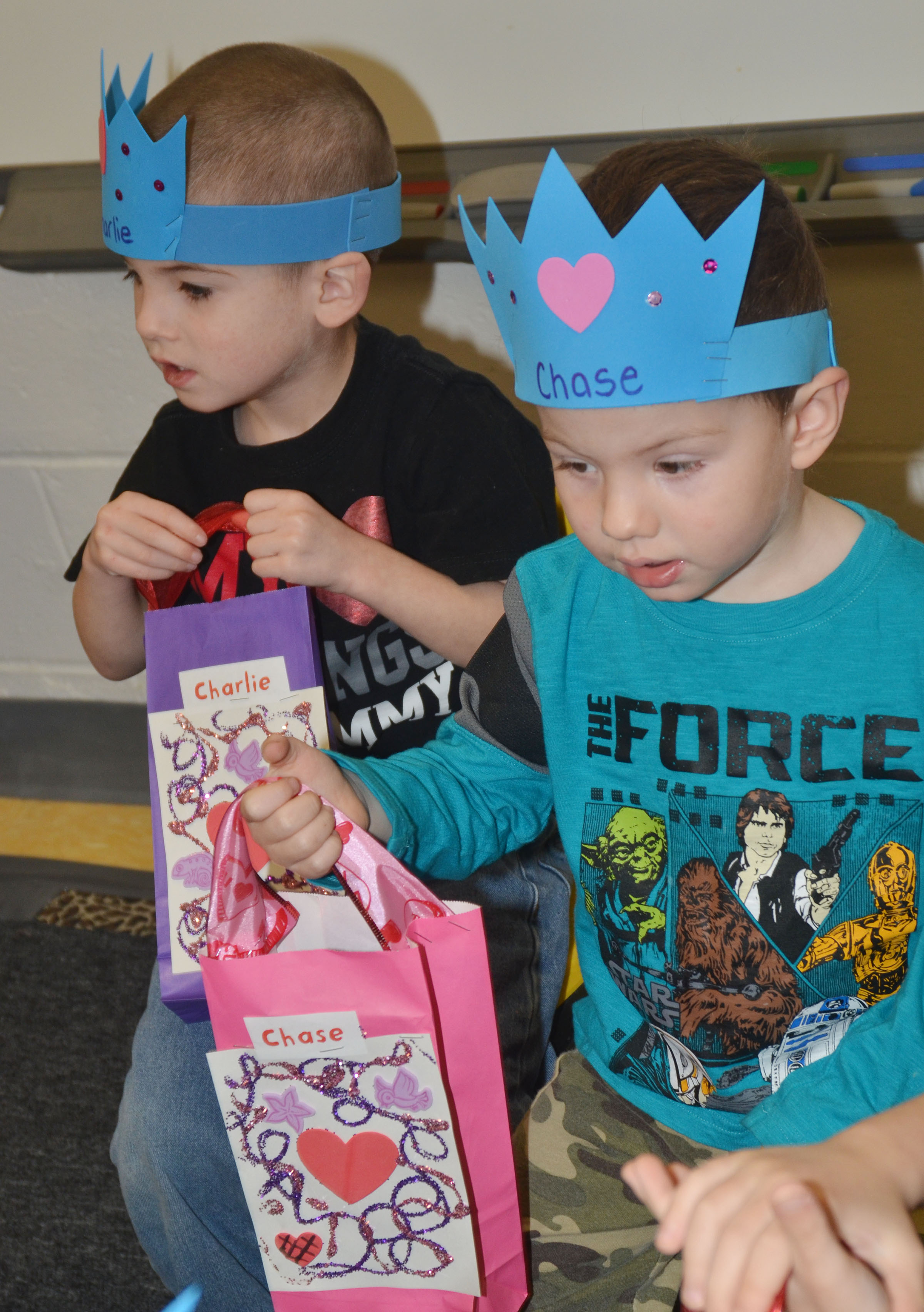 CES preschool students Charlie Woodbury, at left, and Chase Arnett wait as their classmates pass out valentines.