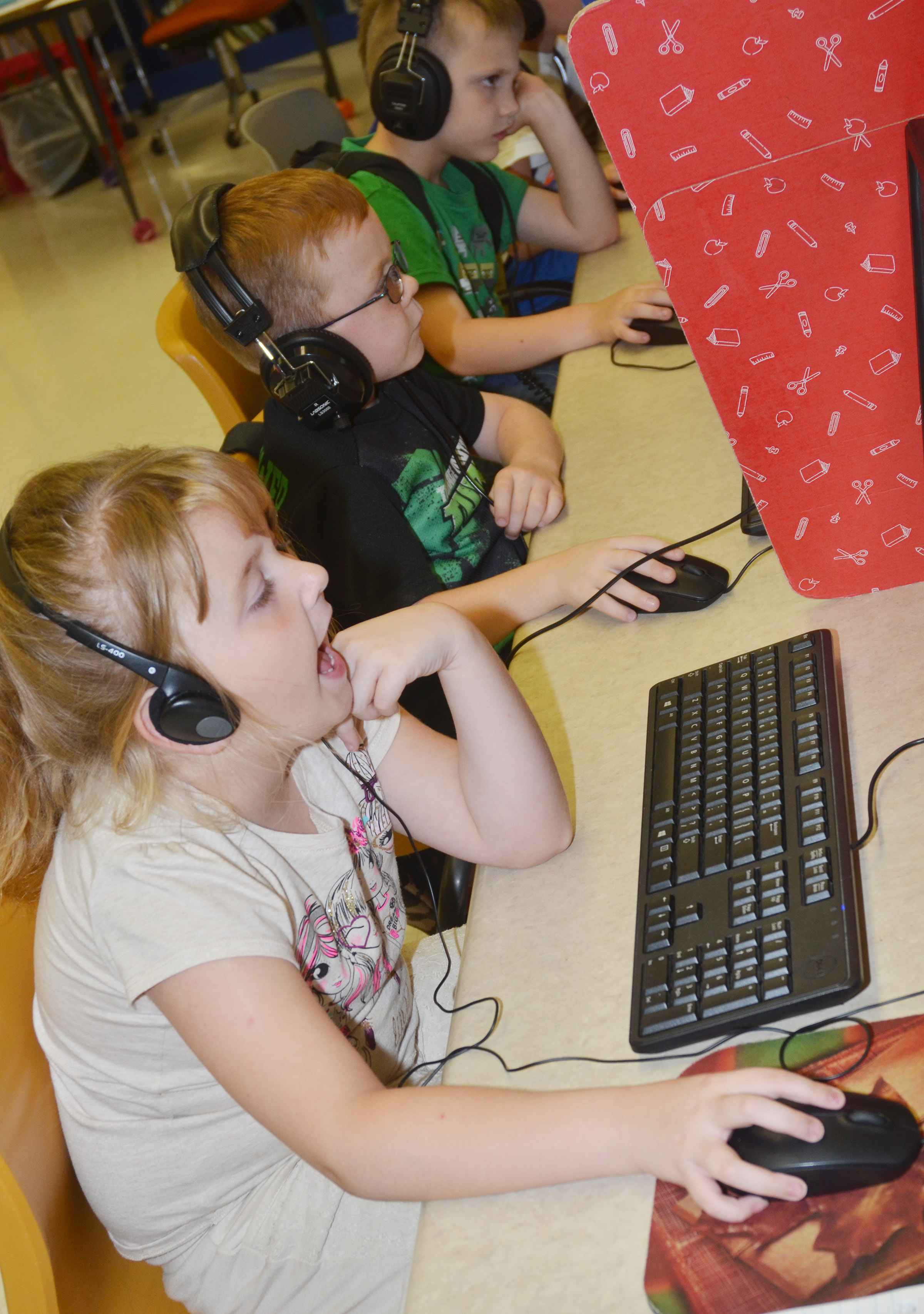 CES first-grader Laurna McKenzie and her classmates use computers to practice their reading skills during the Wings Express program.