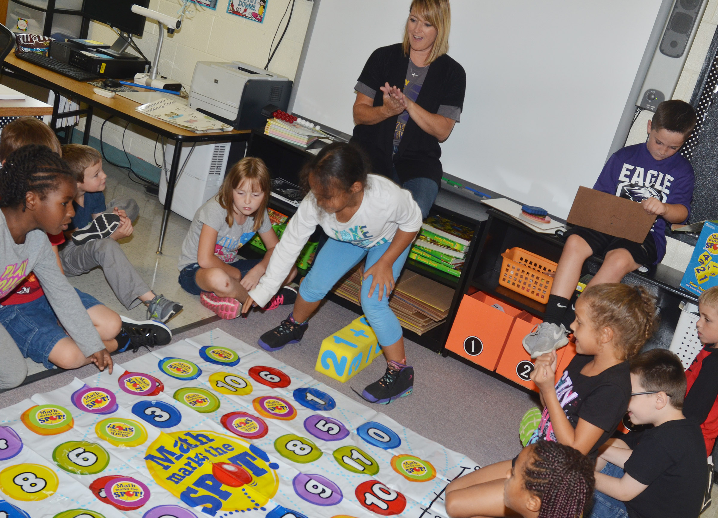 CES teacher Vanessa Adkins plays a math game with second-grade students at Wings Express.
