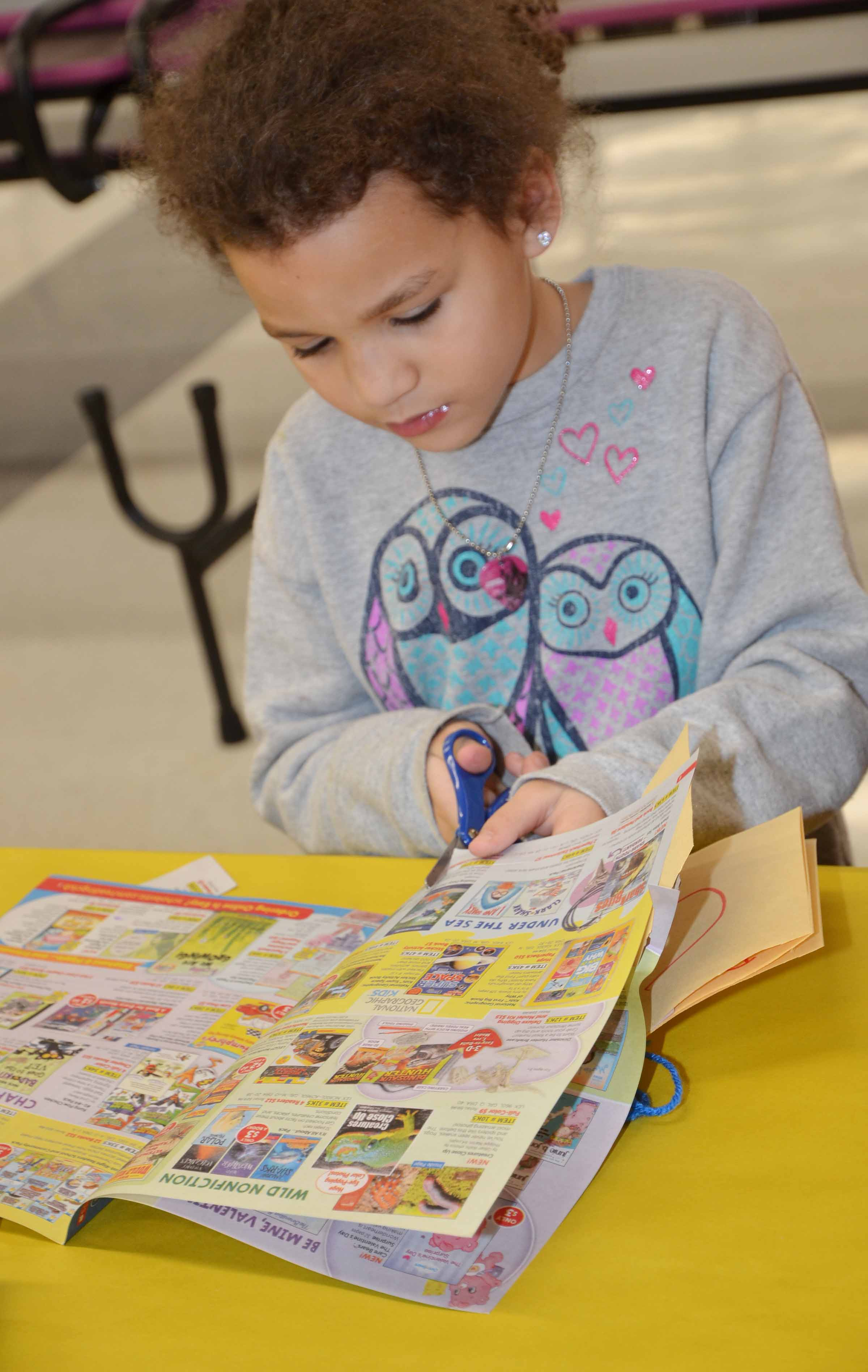 CES kindergartener Aleeya Spaulding cuts out a word for her alphabet book.