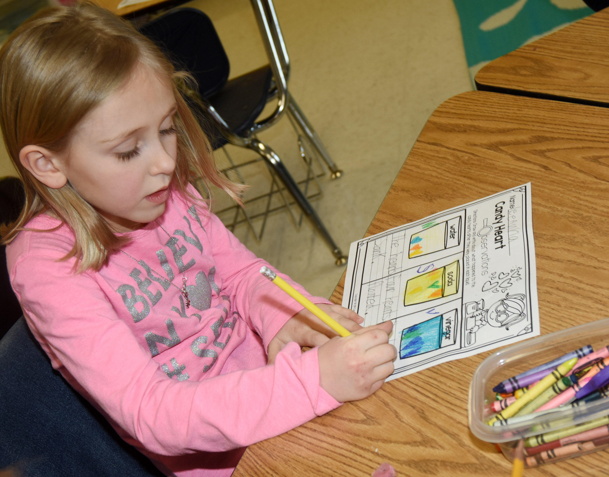 CES first-grader LeeAnna Garvin records what happened when candy hearts are placed in water, soda and vinegar.