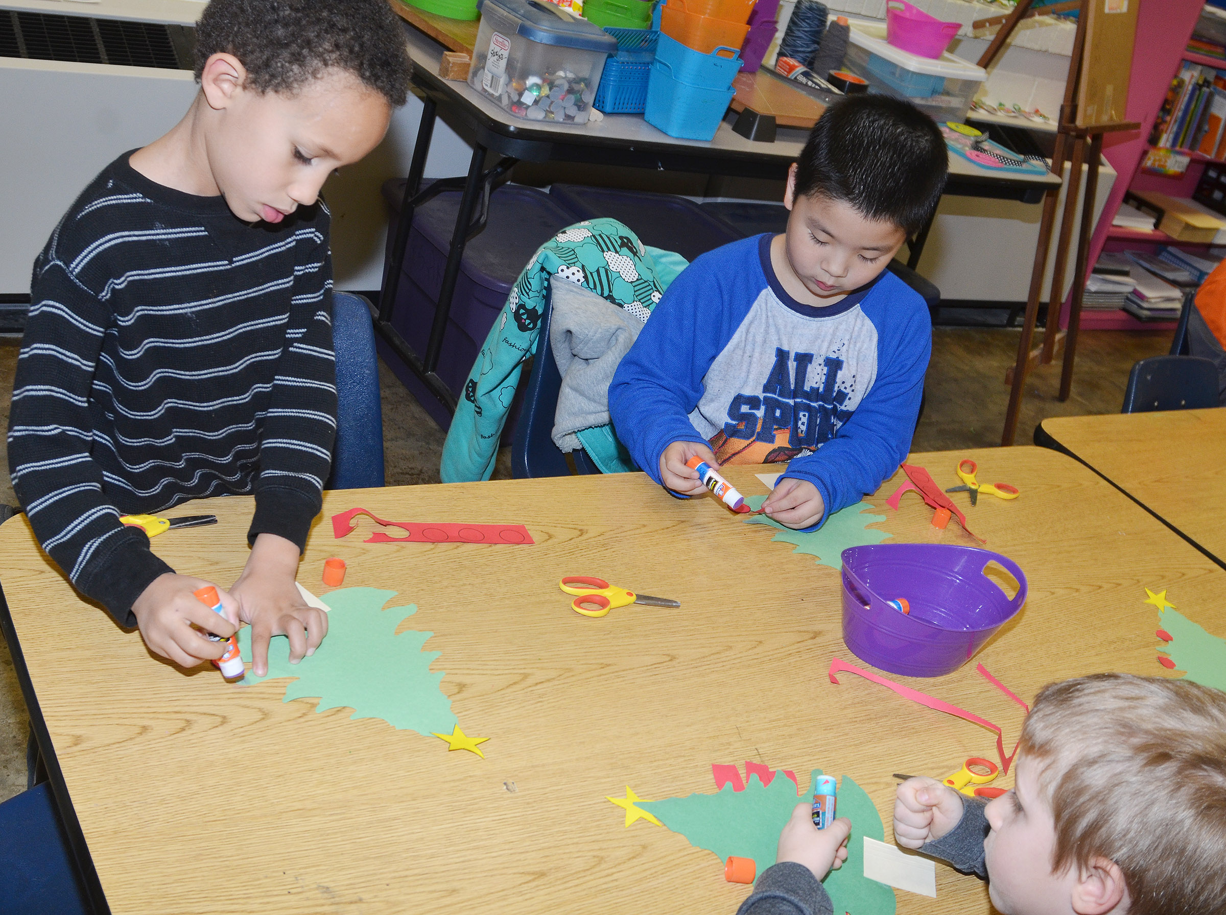 From left, CES kindergarteners Jaxon Williams, William Li and Alex Newcomb glue together their Christmas trees.