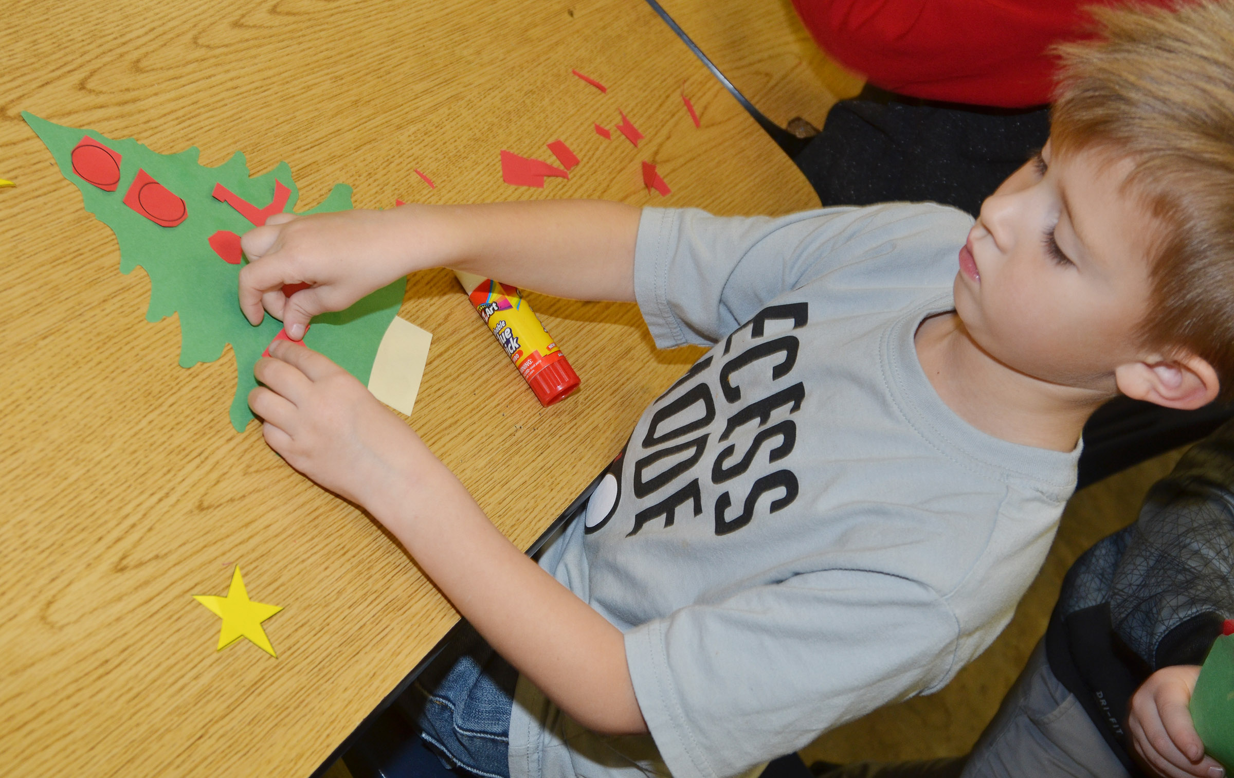 CES kindergartener Andrew Stout glues together his Christmas tree.