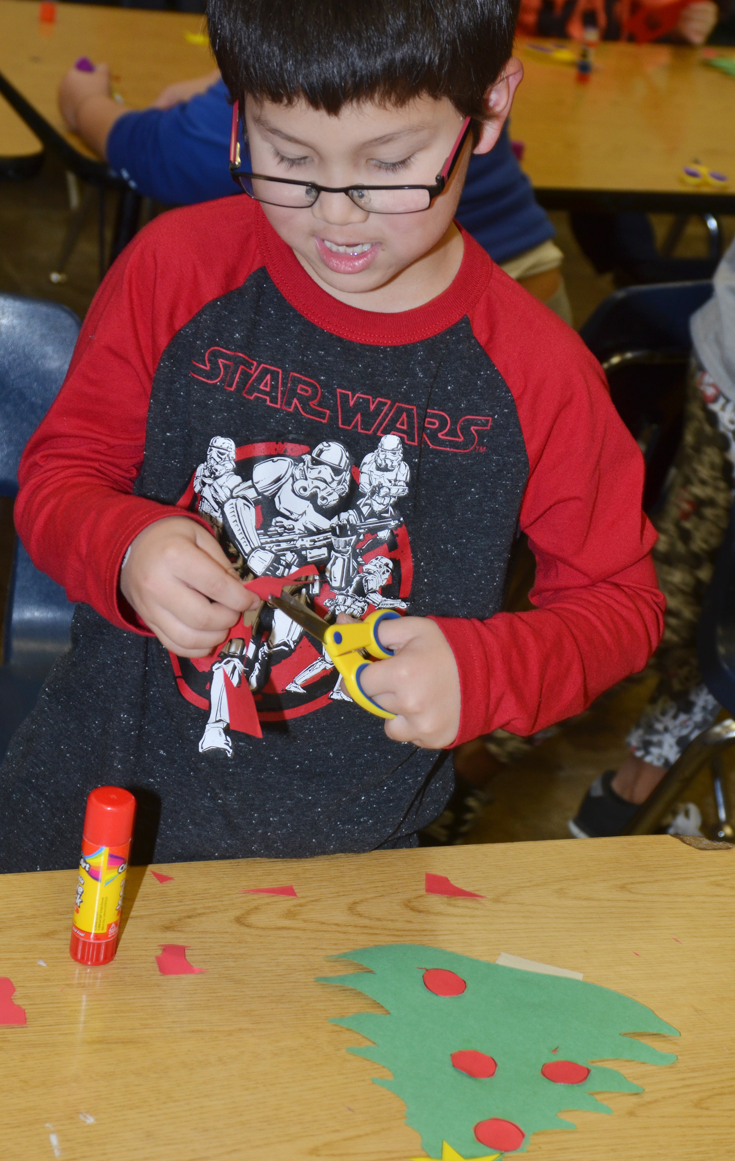 CES kindergartener Victrin Ramsey cuts out the pieces of his Christmas tree.