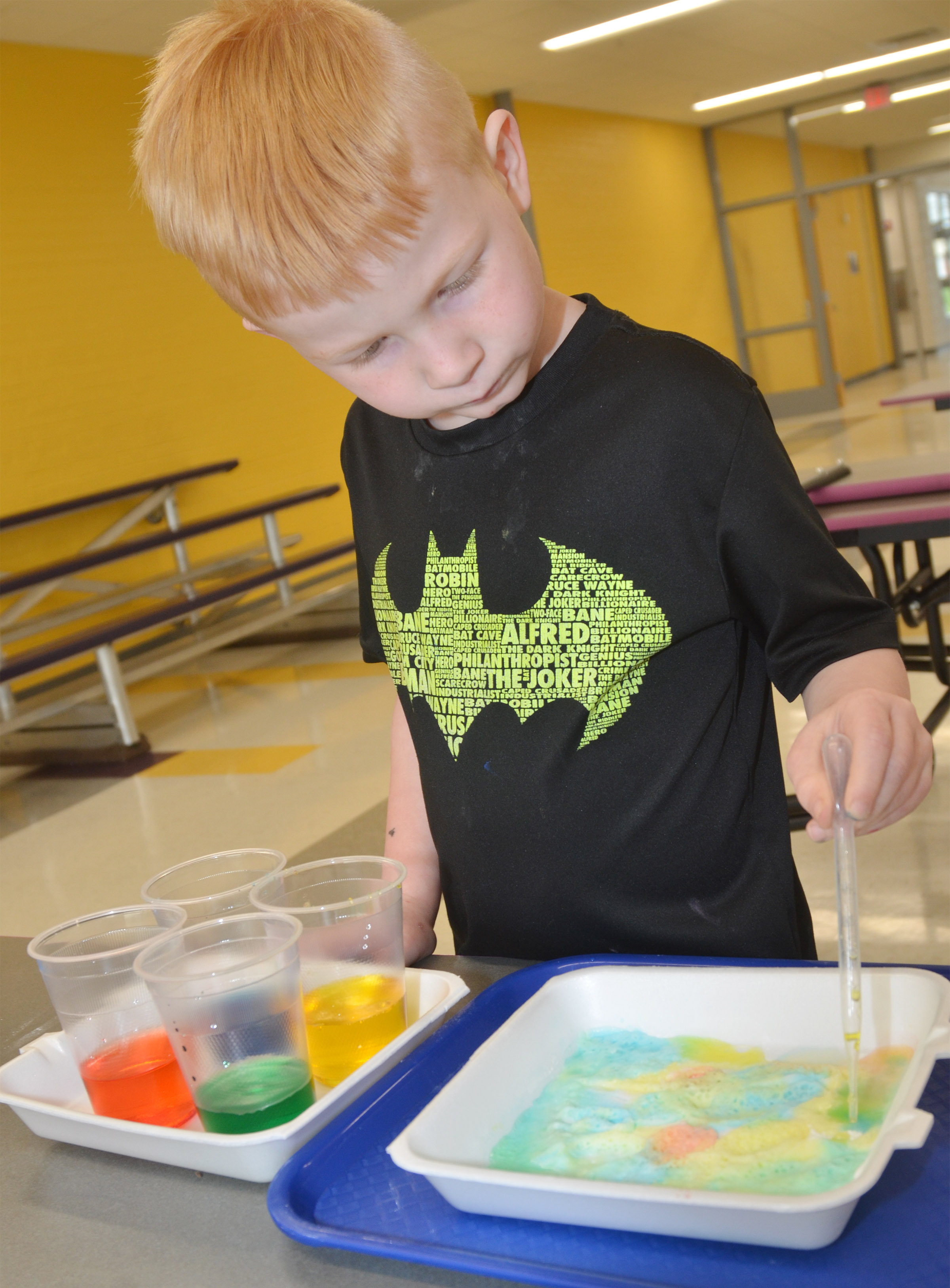 CES kindergartener Jayden Maupin uses baking soda and colored water to make artwork.