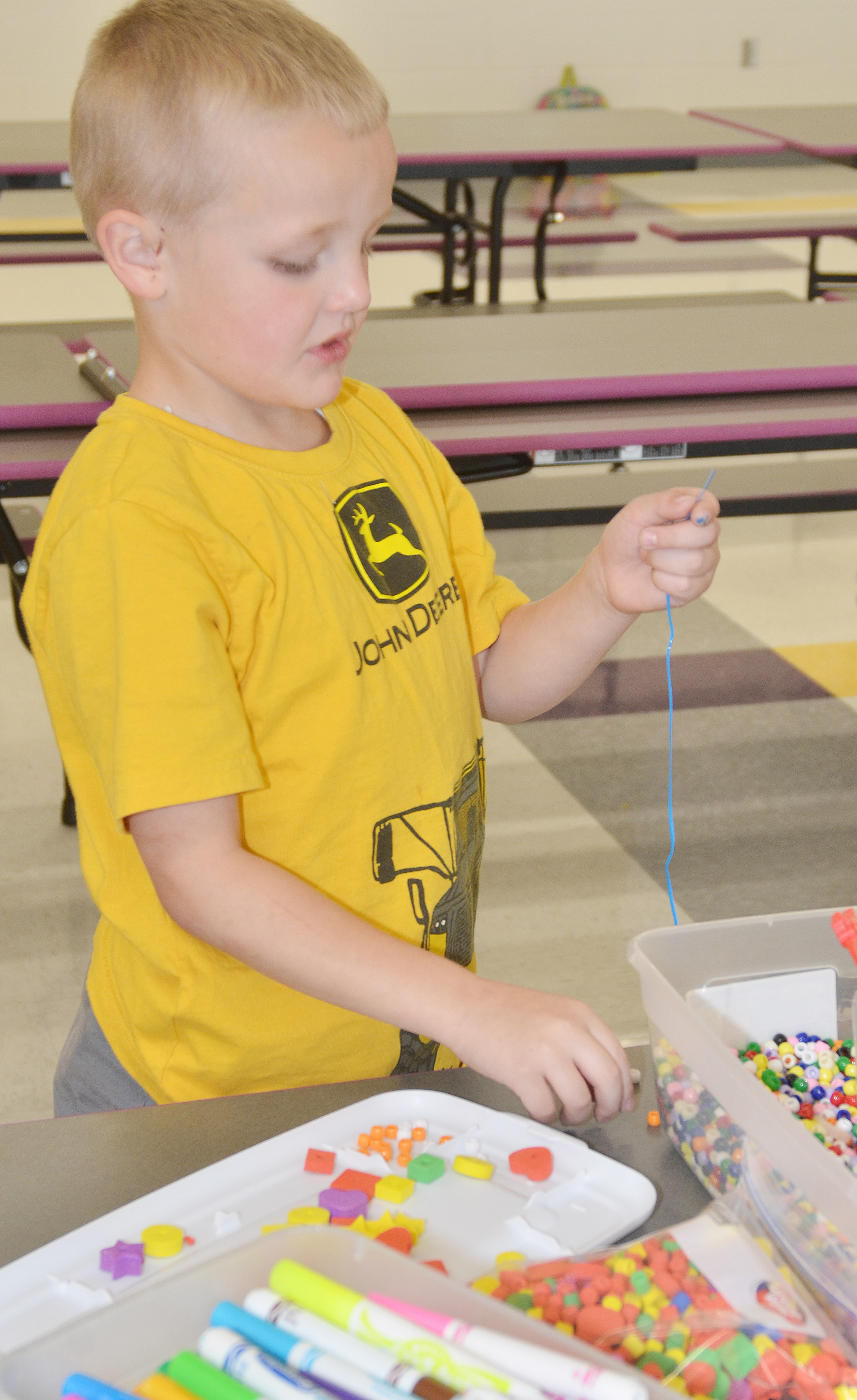 CES kindergartener Tristian Harris makes a necklace.
