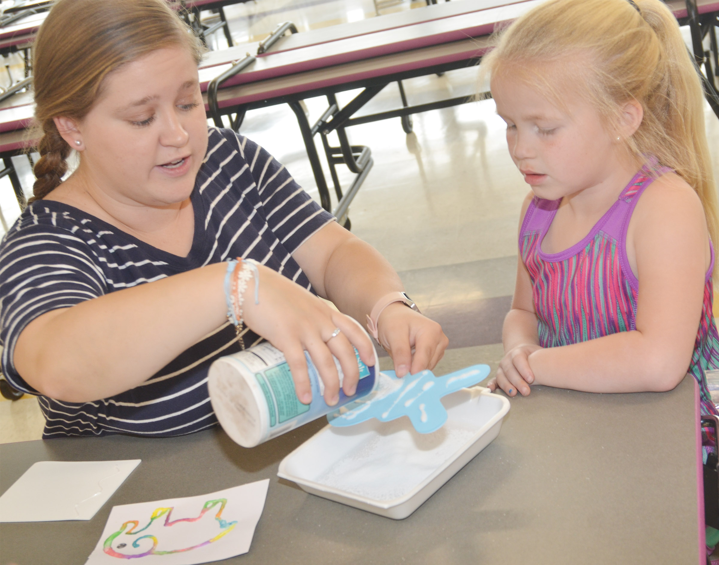 Campbellsville University education student Jordan Bray helps CES kindergartener Lillie Judd add salt to her butterfly so she can paint it.