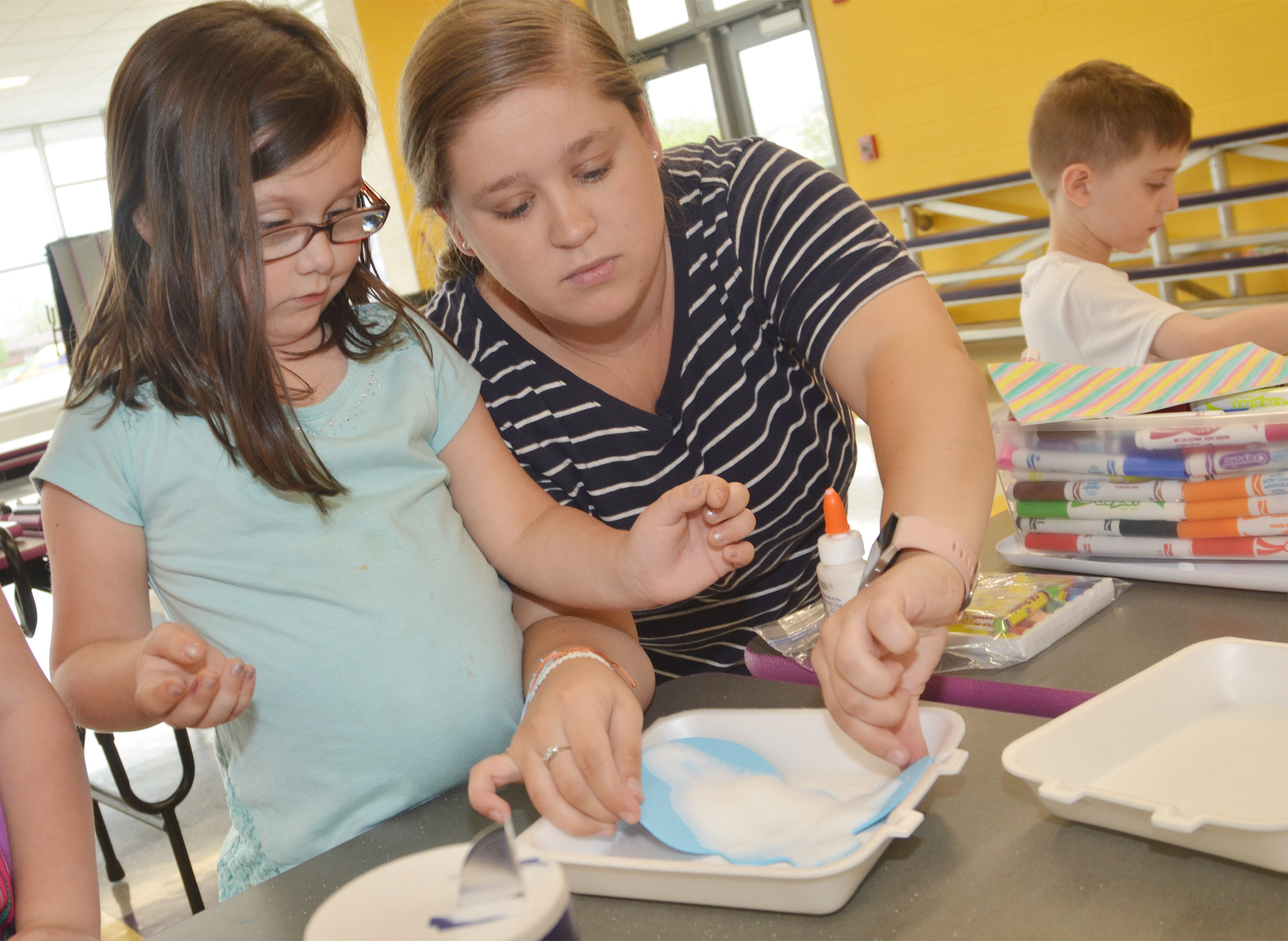 Campbellsville University education student Jordan Bray helps CES kindergartener Trinity Clark add salt to her rabbit so she can paint it.