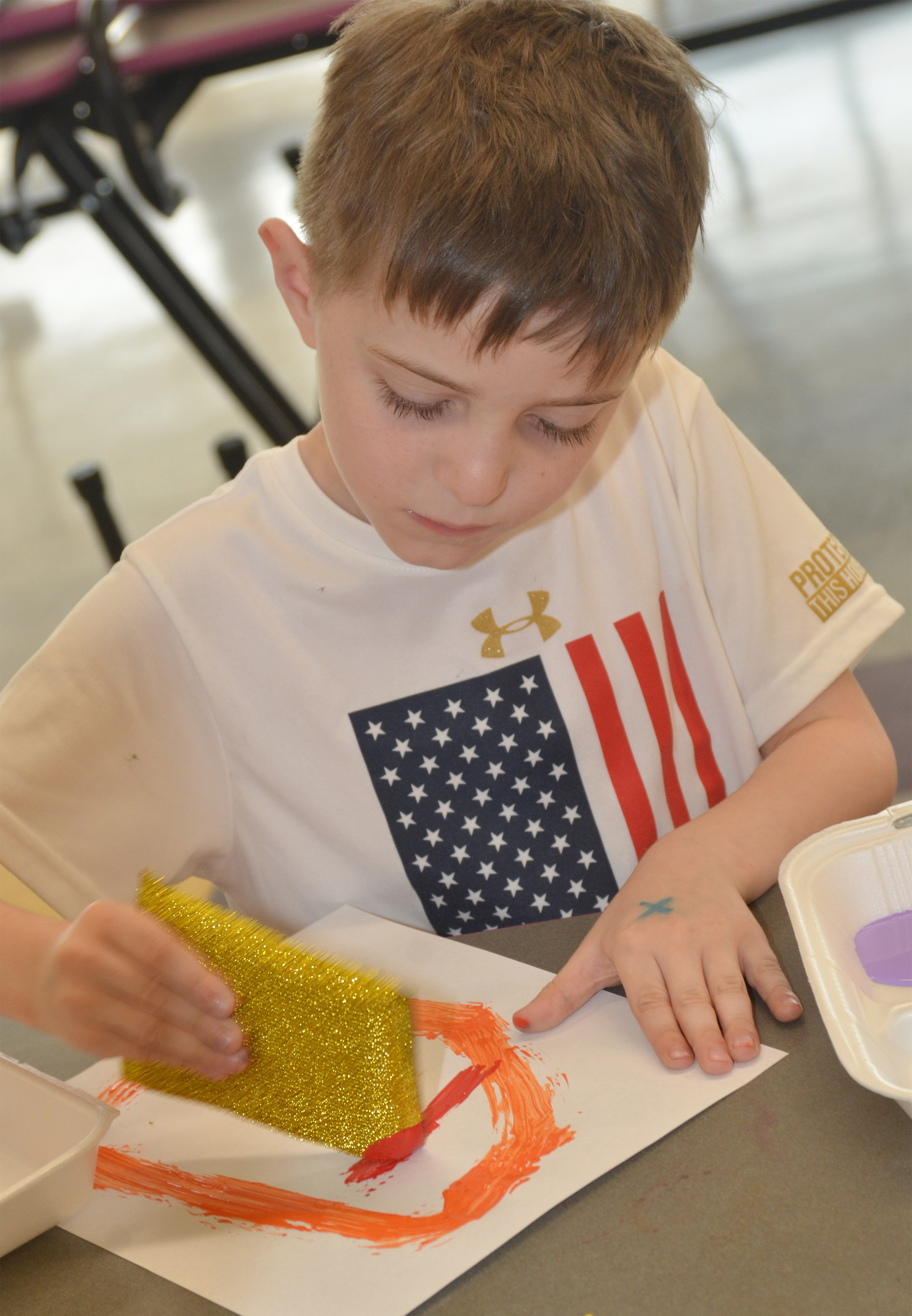CES kindergartener Caleb Goodson paints with a sponge.
