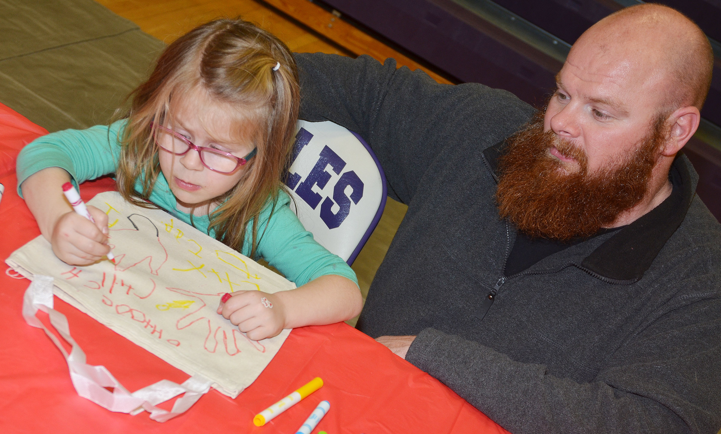 CES preschool student Charlotte Coots makes a tote bag with her father, T.J. Coots.