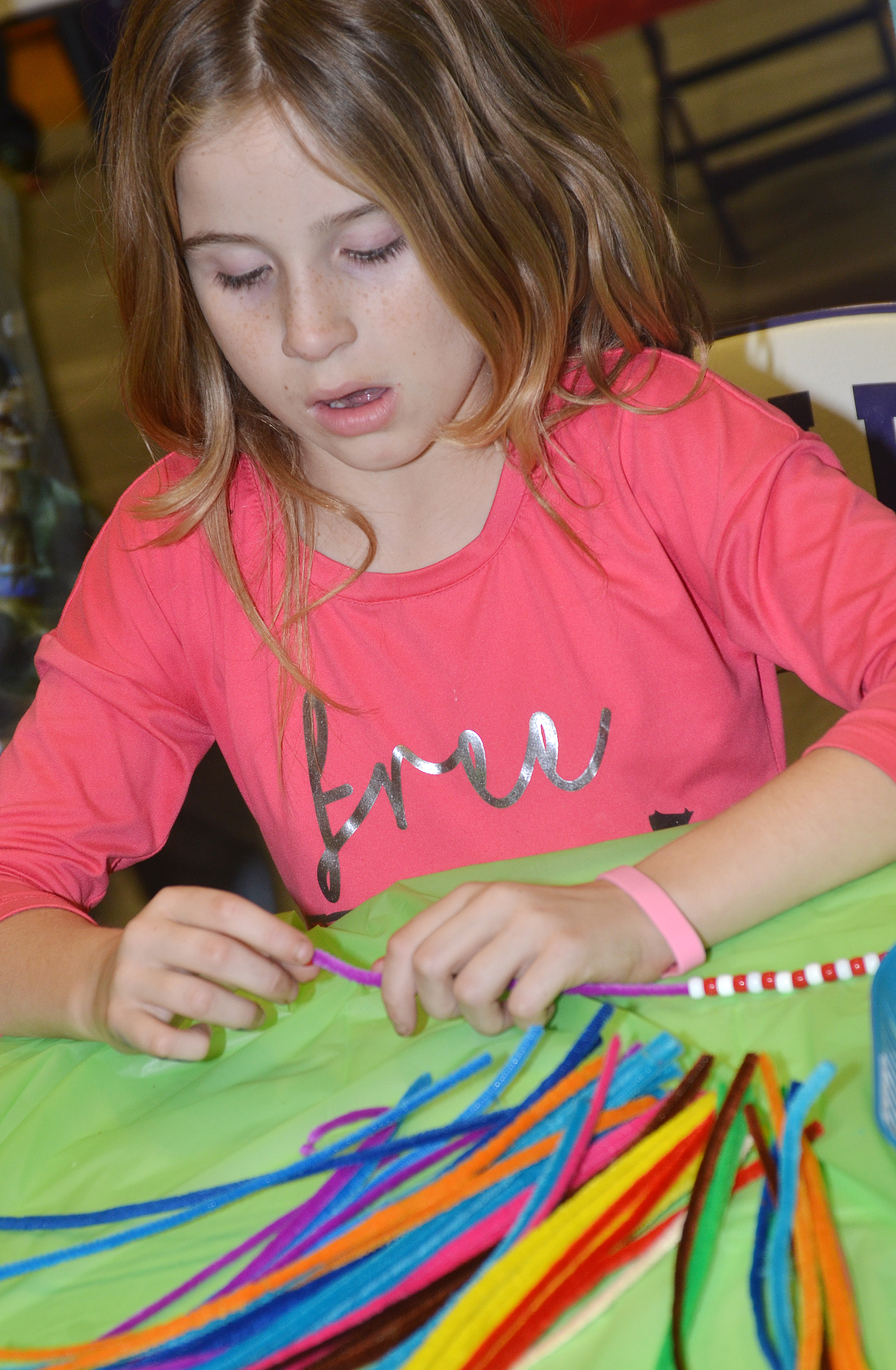 CES fourth-grader Raegan Hayes makes a bracelet.