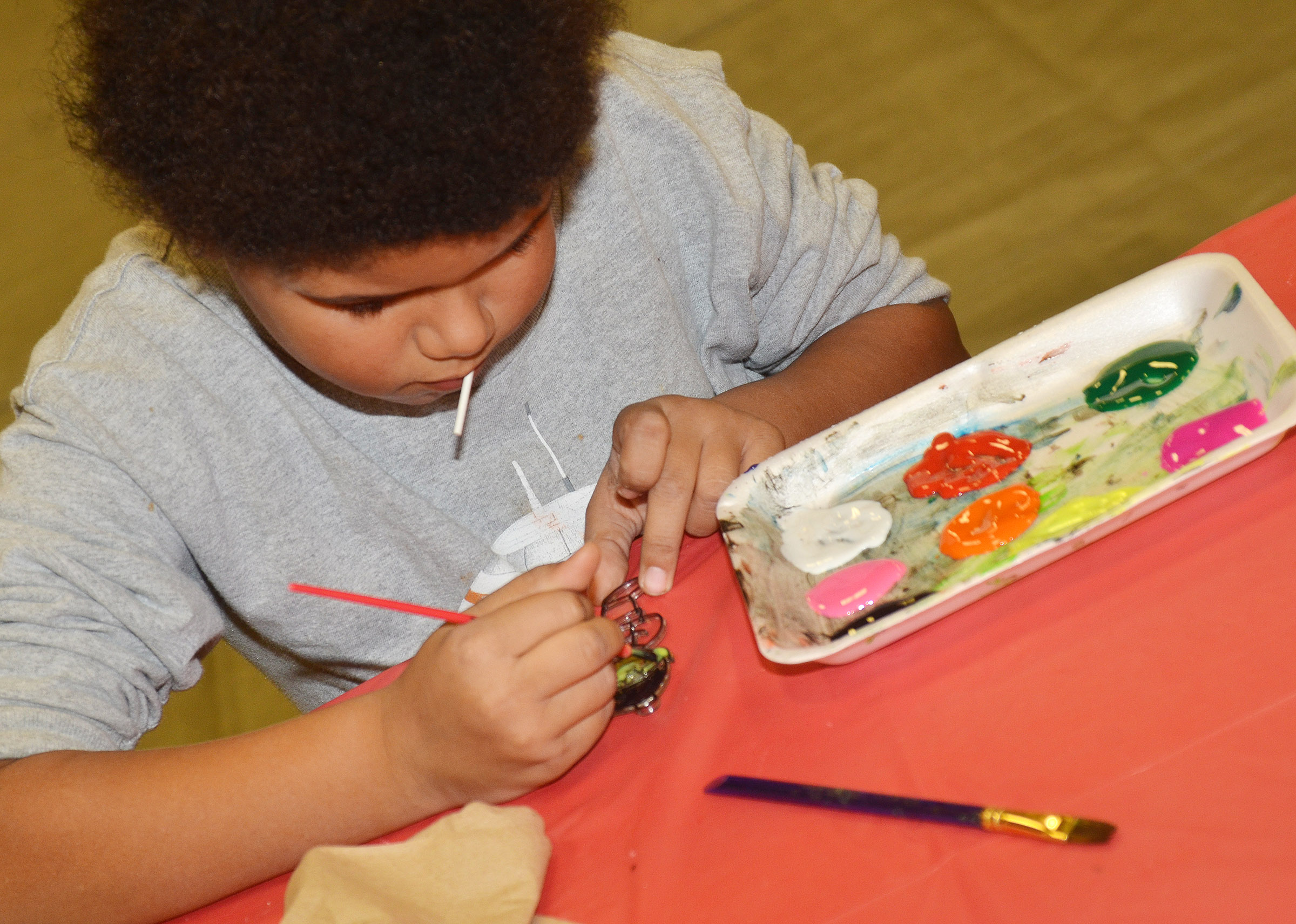 CES second-grader Navon Copeland paints an ornament.