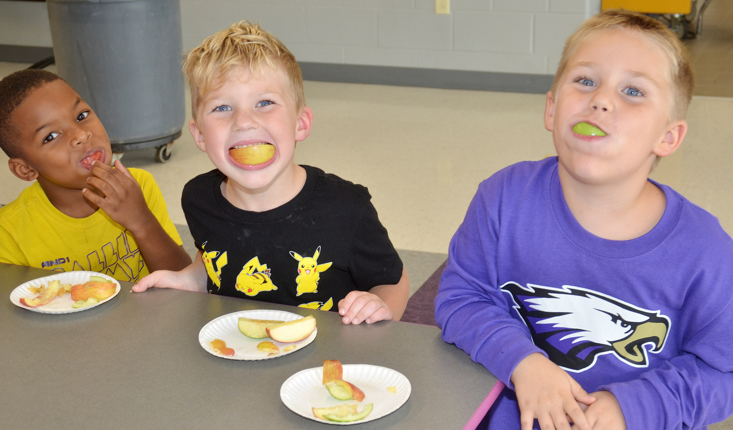 CES Wings Express kindergarten student Victrin Ramsey samples an apple.