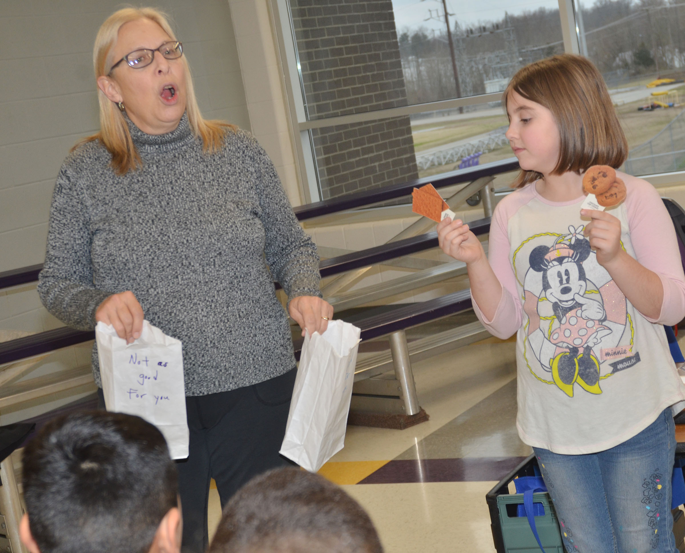 CES third-grader Adrianna Garvin and Angie Freeman, expanded foods and nutrition program assistant at Taylor County Extension Office, ask which is healthier, graham crackers or chocolate chip cookies.