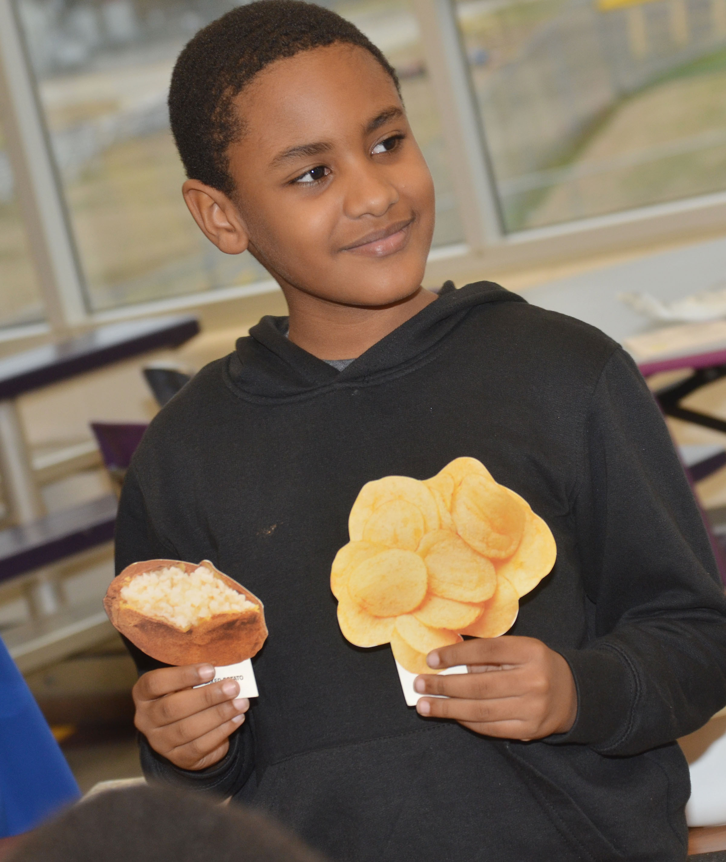 CES third-grader Shaiden Calhoun asks his classmates which is healthier, baked potatoes or potato chips.