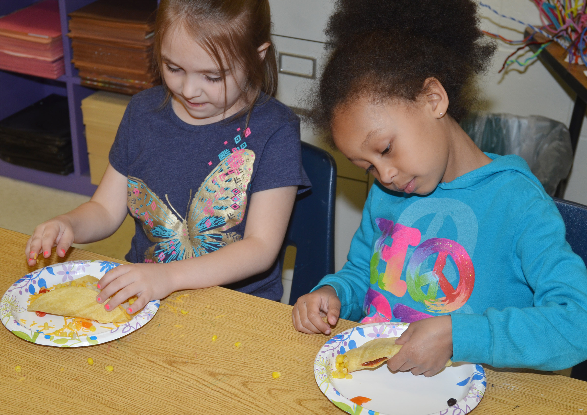 CES kindergarteners Aubrey Allen, at left, and Elyzabeth Fisher enjoy their Mexican pizzas.