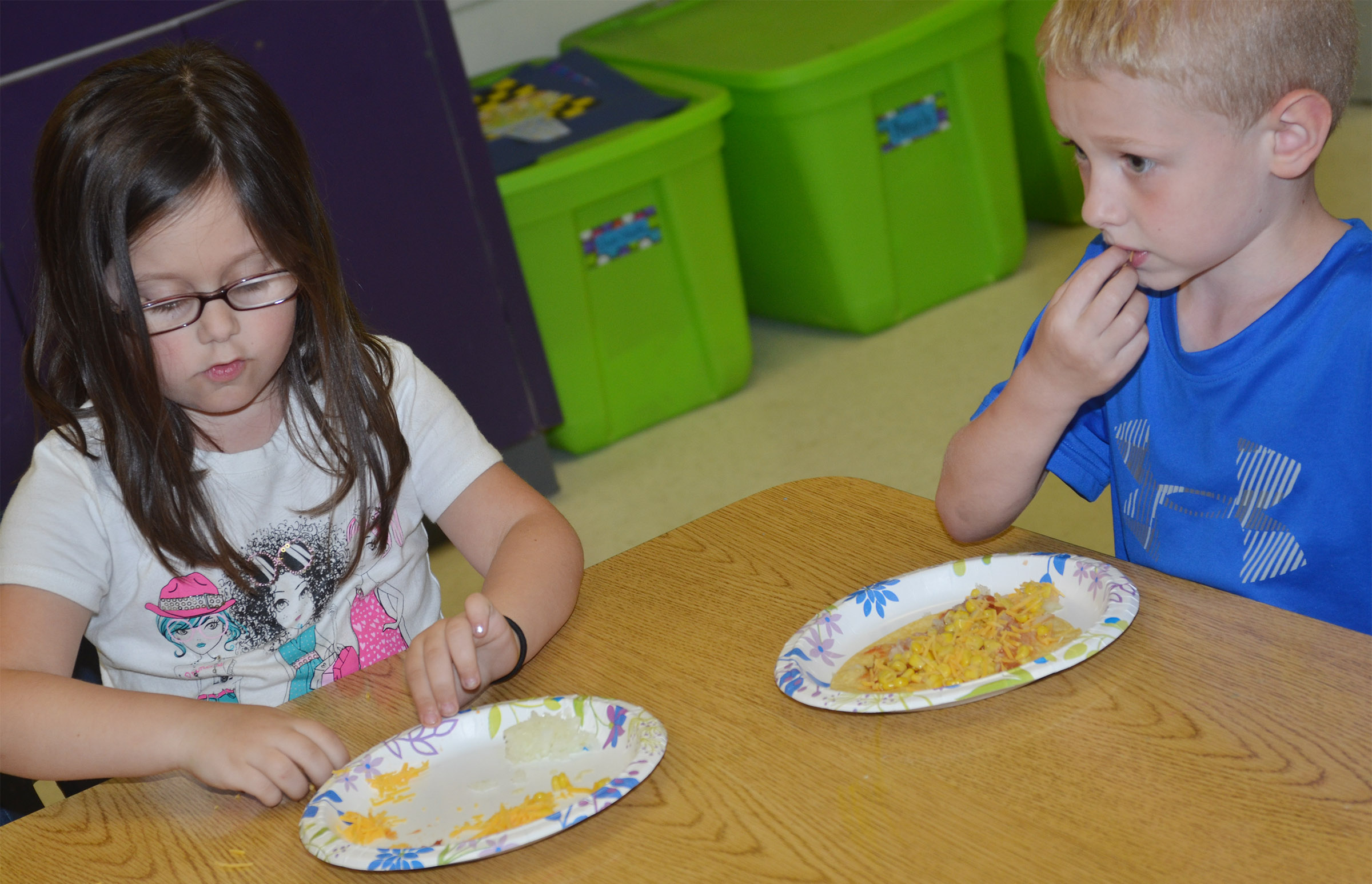 CES kindergarteners Trinity Clark, at left, and Jackson Wright enjoy their Mexican pizzas.