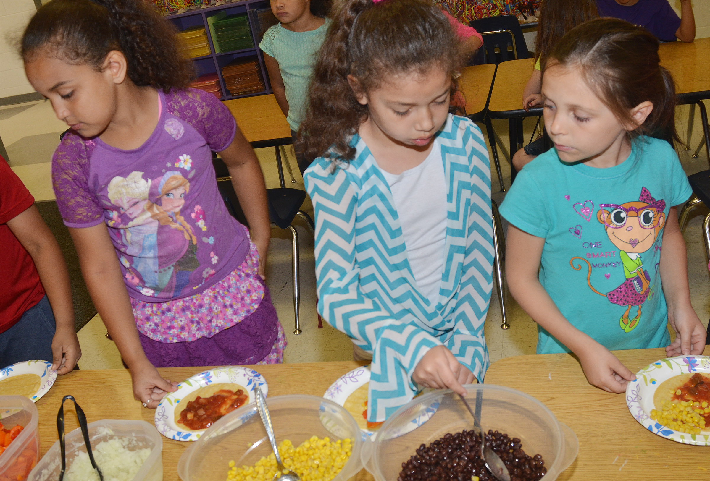 CES first-graders, from left, Maleigha Travis, Ammarissa Nunez and Serenity Taylor make their own Mexican pizzas.