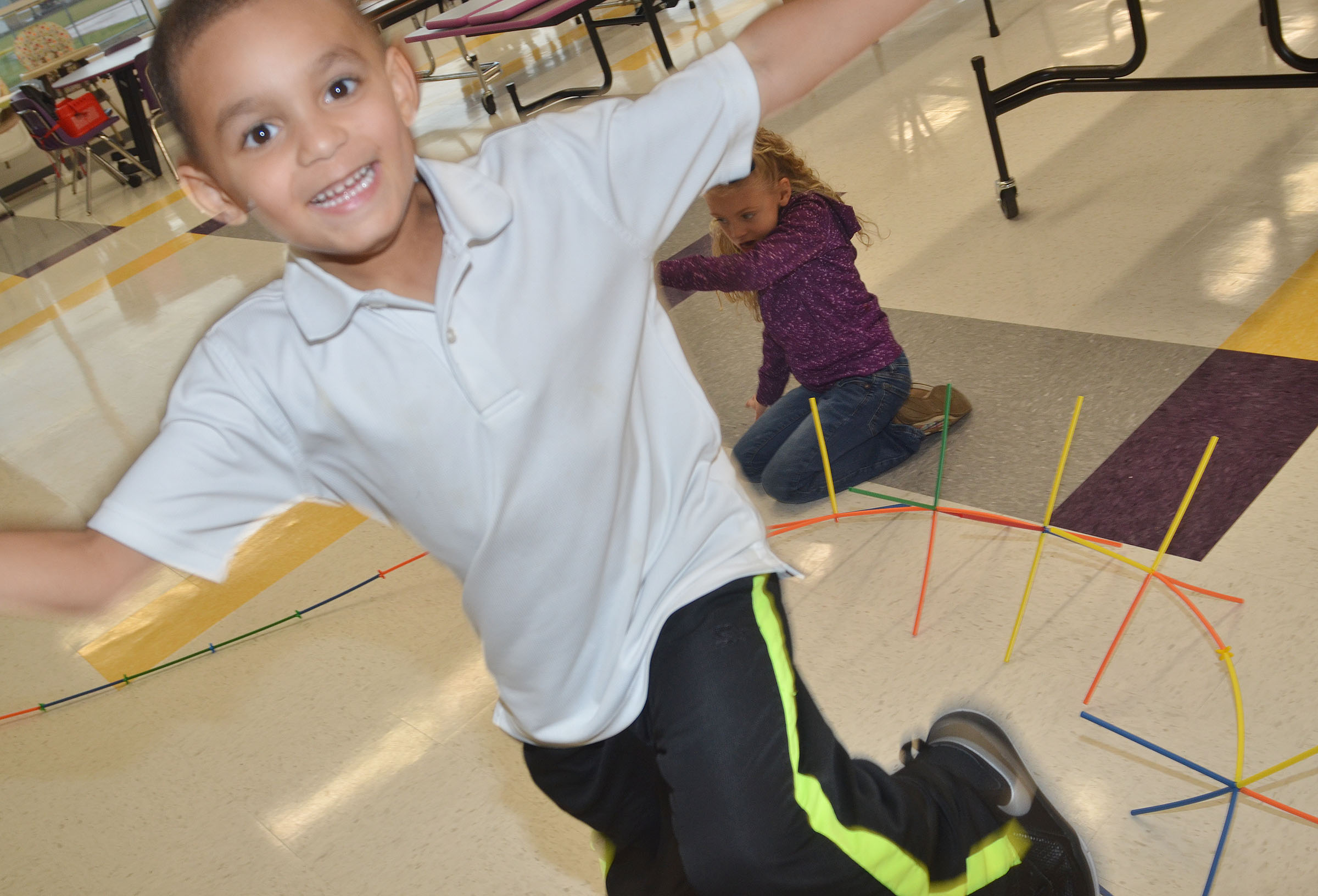 CES kindergartener Quincy Travis runs around a race track that he and his classmates built.