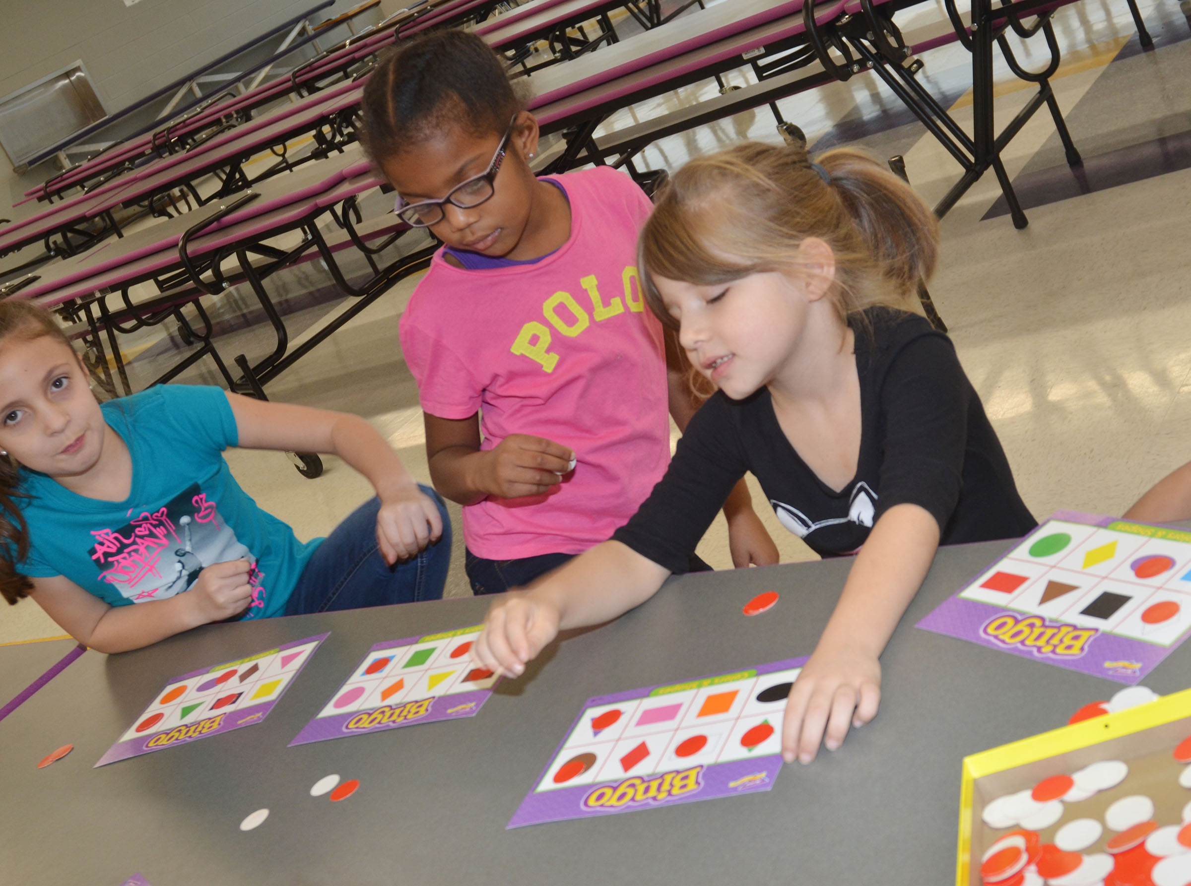 CES first-graders, from left, Lillian Martin, Willow Griffin and Kenady Gabehart play shapes Bingo.