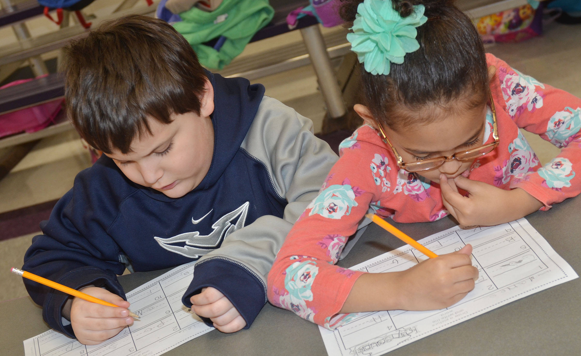 CES kindergarteners Cloud Malone, at left, and Marlee Dickens practice writing uppercase and lowercase letters.