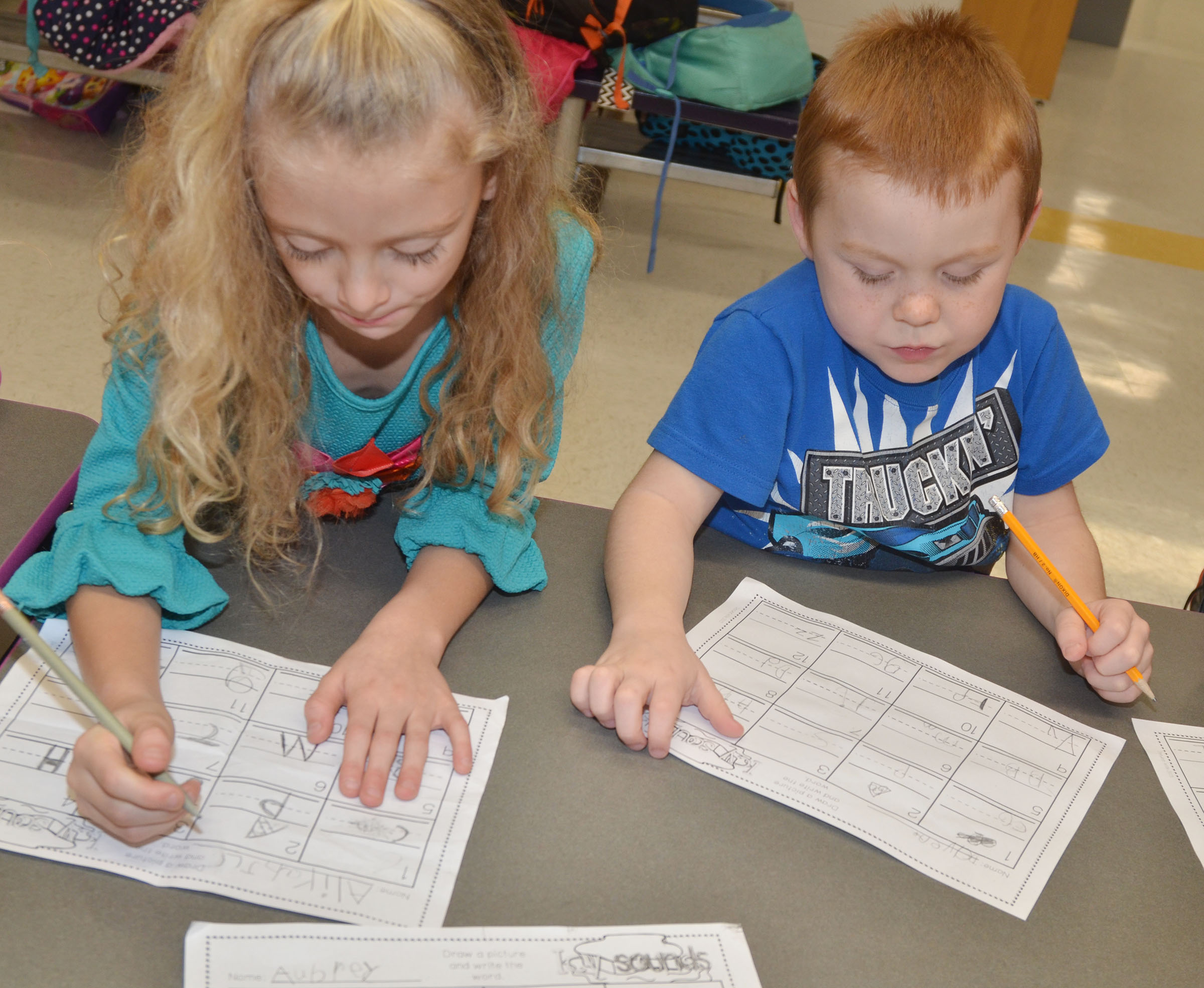 CES kindergarteners Aliyah Litsey, at left, and Daven Davis practice writing uppercase and lowercase letters.