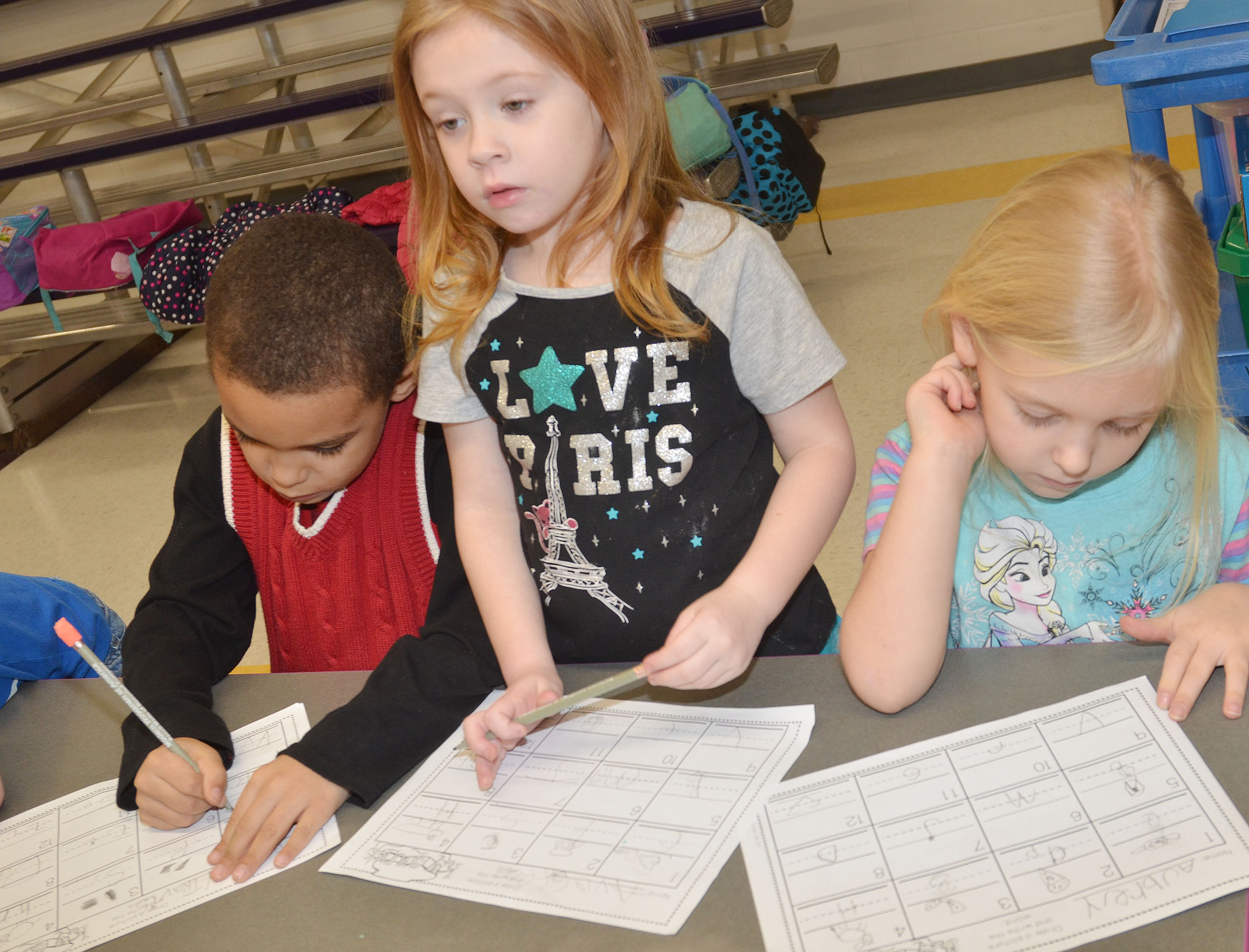 From left, CES kindergarteners Quincy Travis, Ava Caffee and Aubrey Novak practice writing uppercase and lowercase letters.