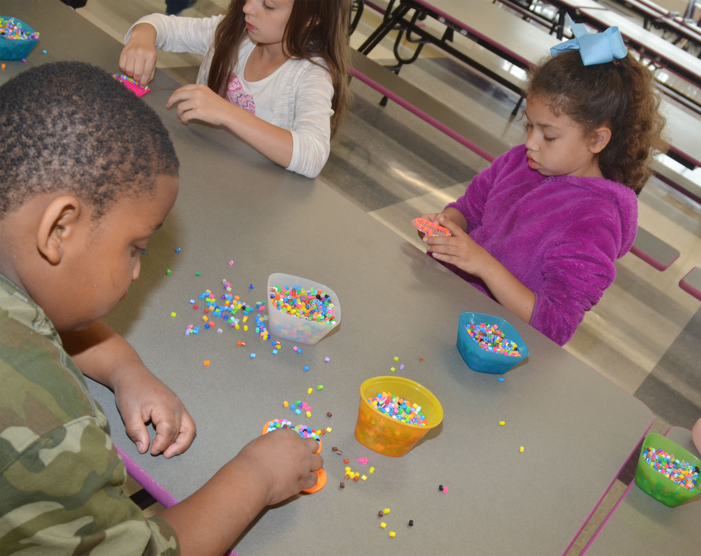 From left, CES kindergartener Malachi Conner and first-graders Lillian Martin and Ammarissa Nunez use beads to make their own creations.