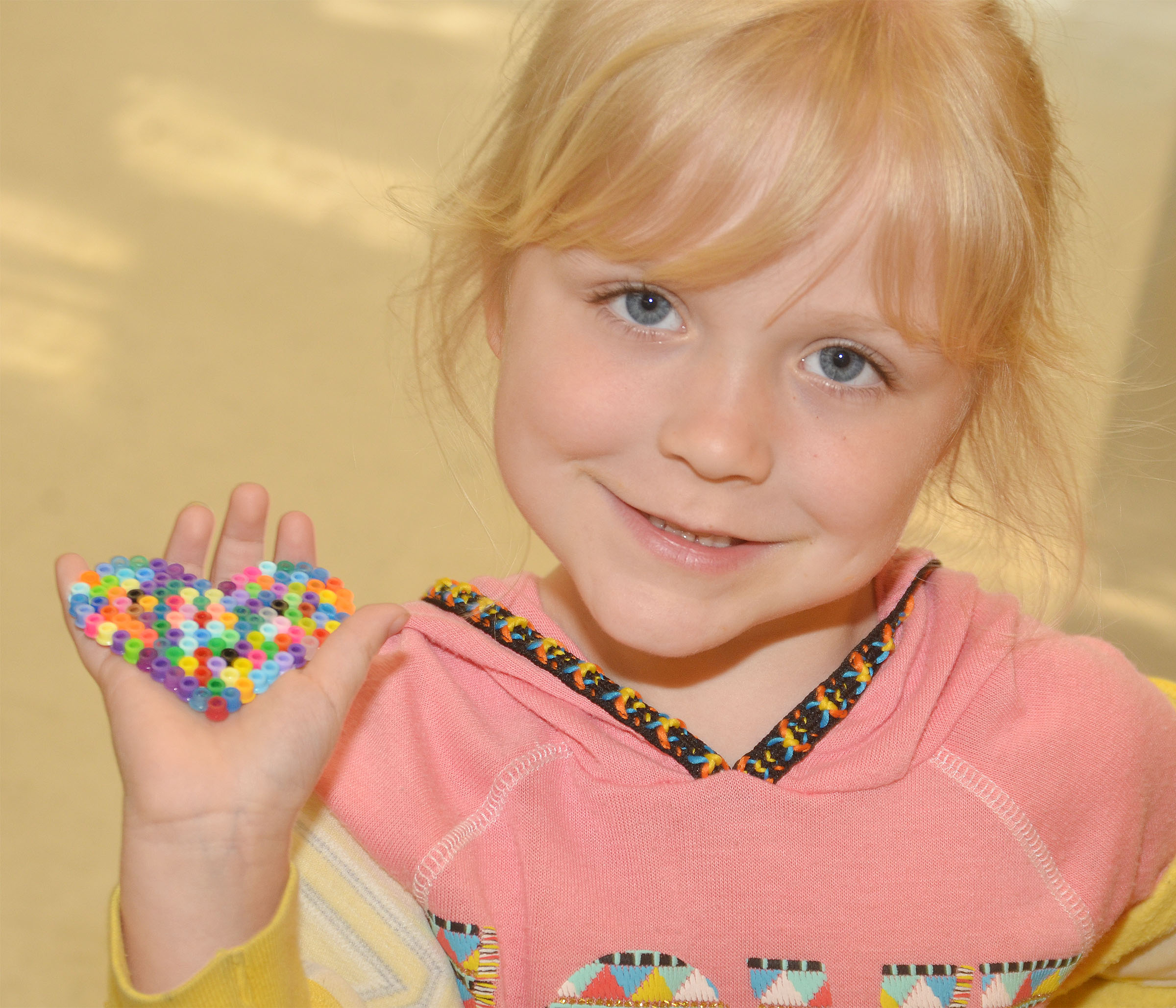 CES kindergartener Ava Bennett-Marr holds the heart she made out of beads.