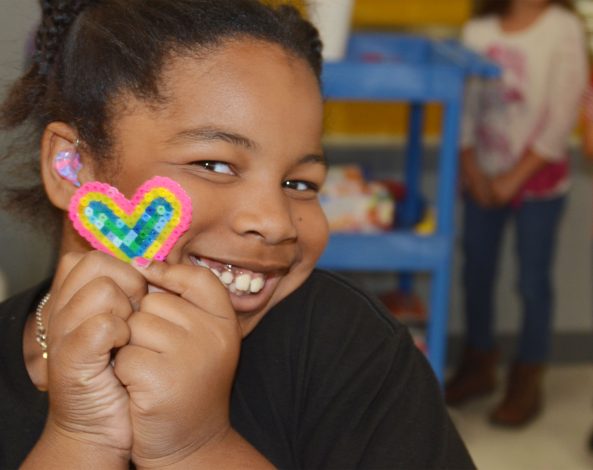 CES third-grader KaMiya Williams holds the heart she made out of beads.