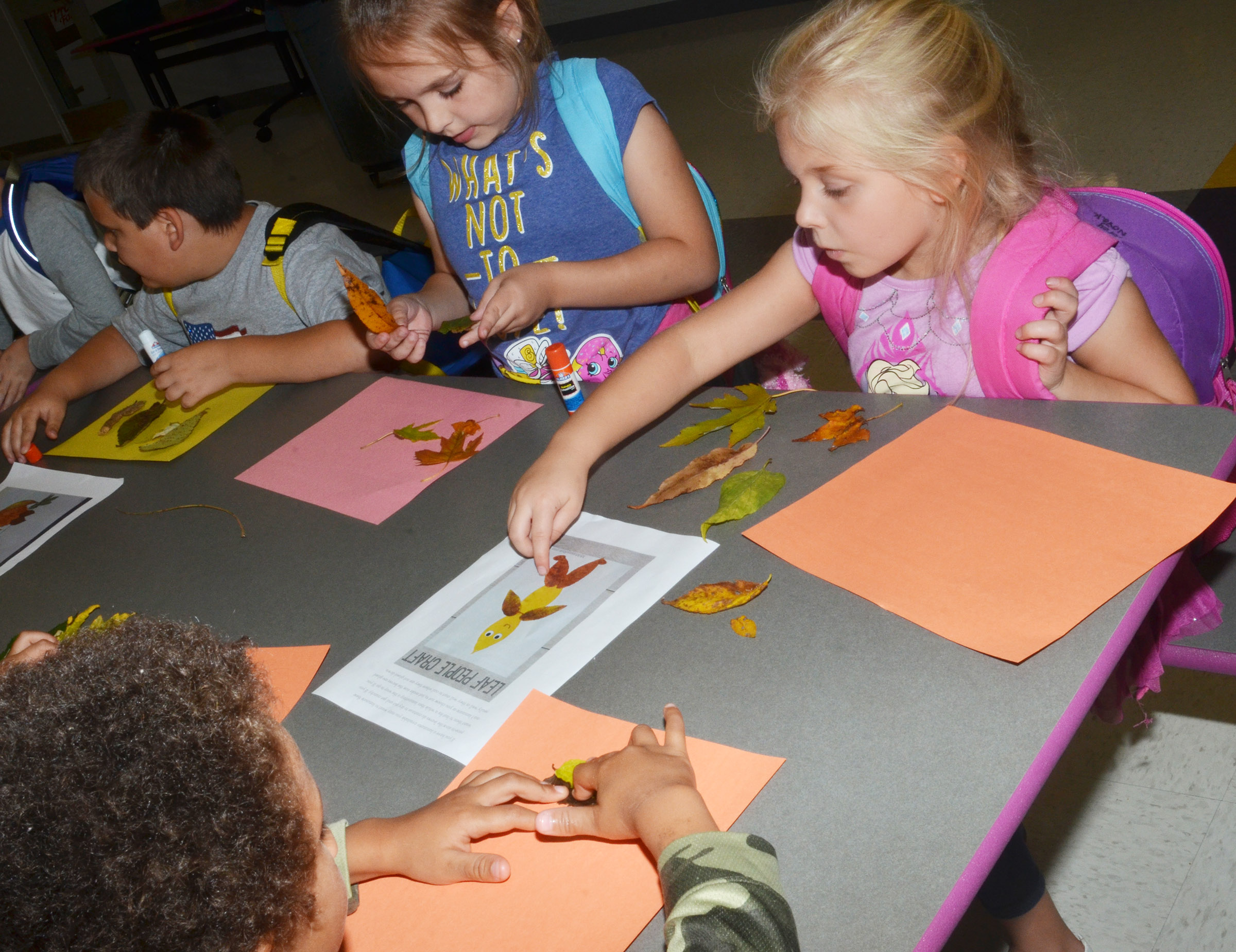 CES first-graders Aubrey Allen, at left, and Aubrey Novak use leaves to make animals.