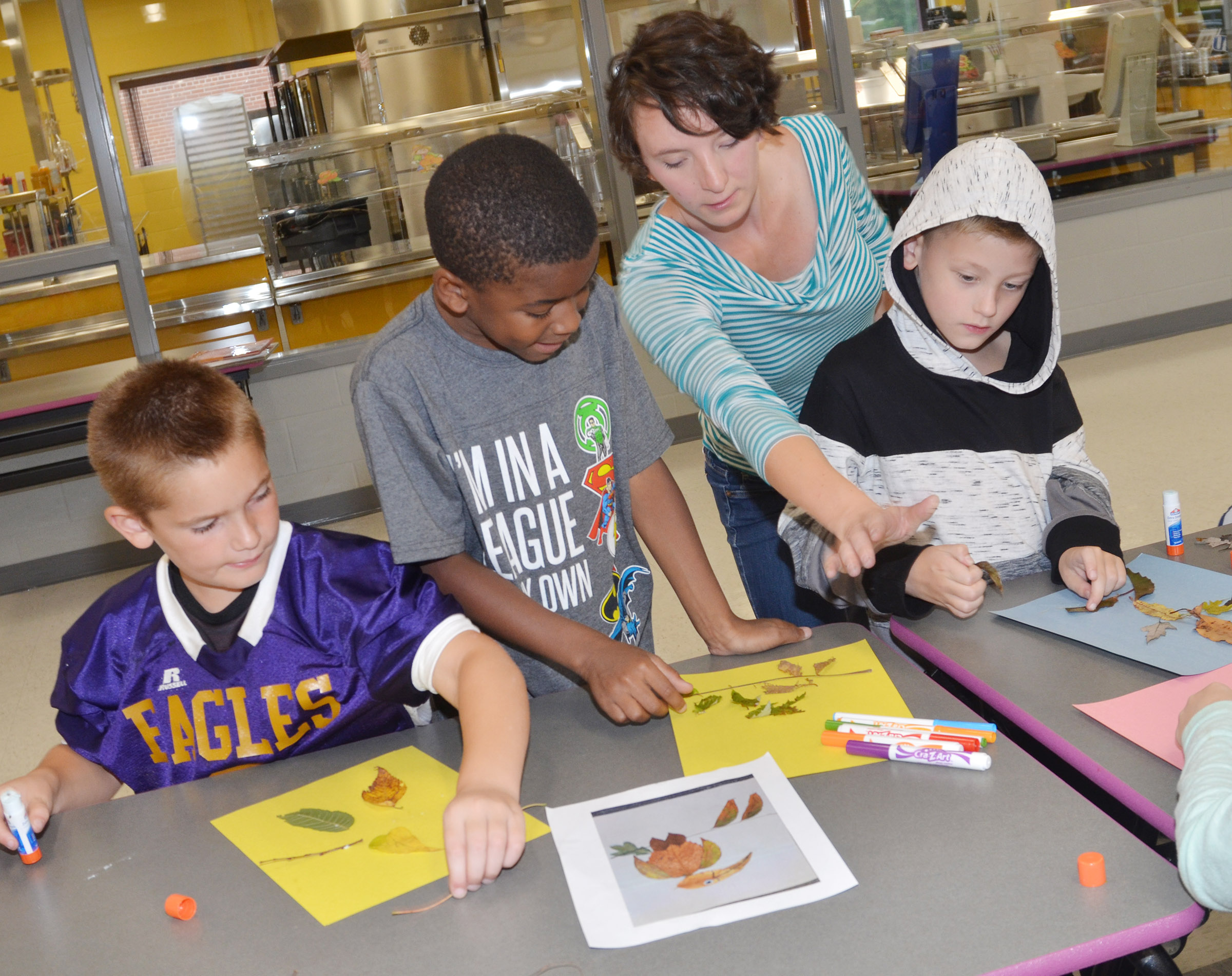 Kelsie Pepper from the Taylor County Public Library helps CES third-graders, from left, Sean Welch, Kae'vin Spaulding and Malachi Sanford make animals out of leaves.
