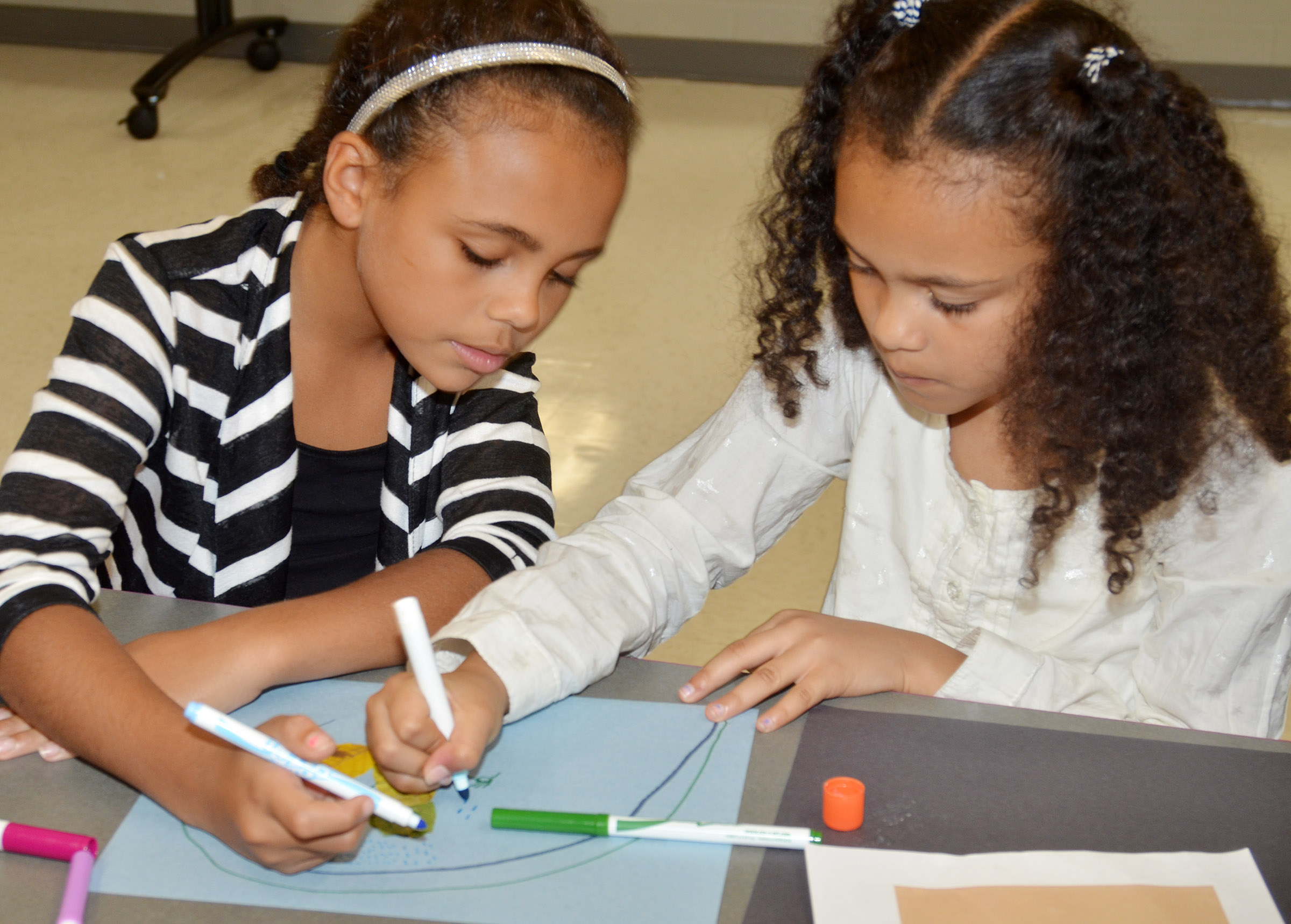 CES third-graders Braelyn Taylor, at left, and Alexia Howard draw on their leaf animal.
