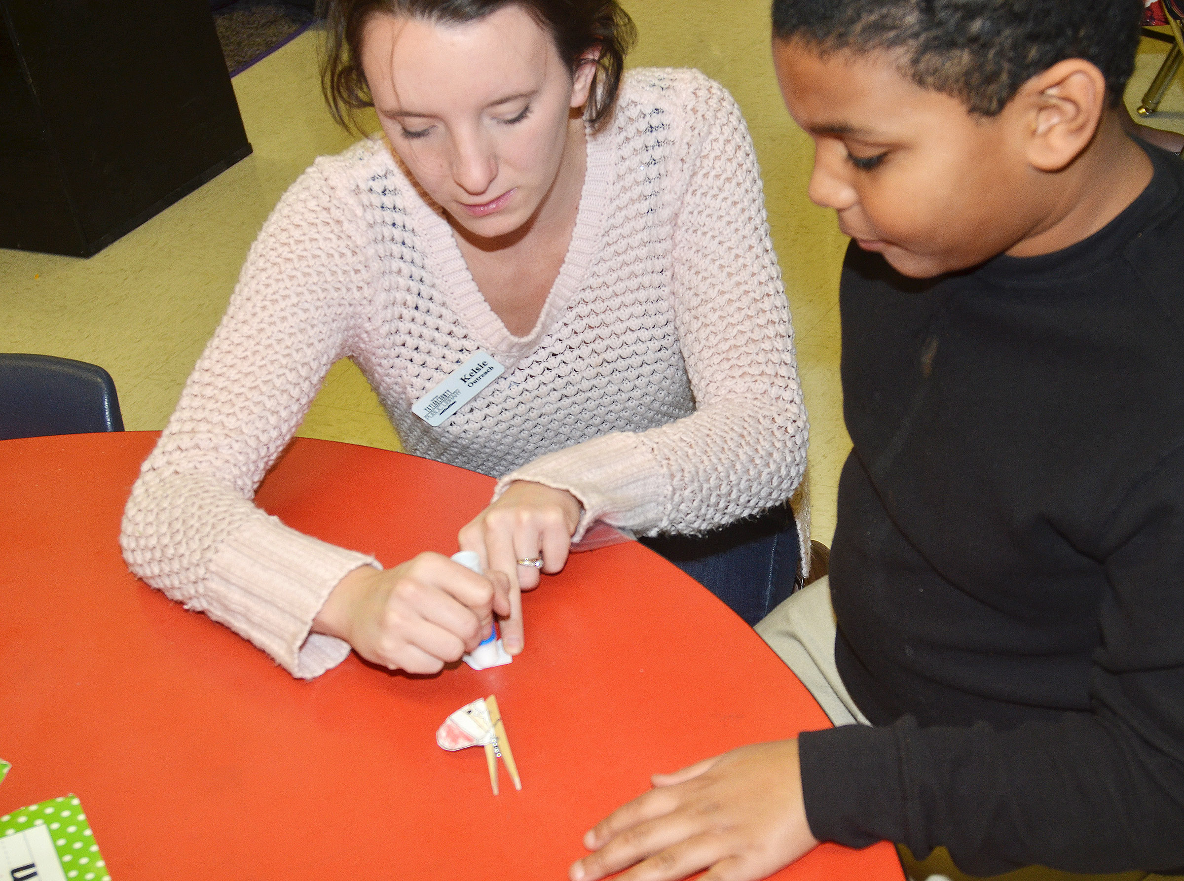 Kelsie Pepper from the Taylor County Public Library helps CES third-grader Zaemar Hoskins make his Santa clothespin.