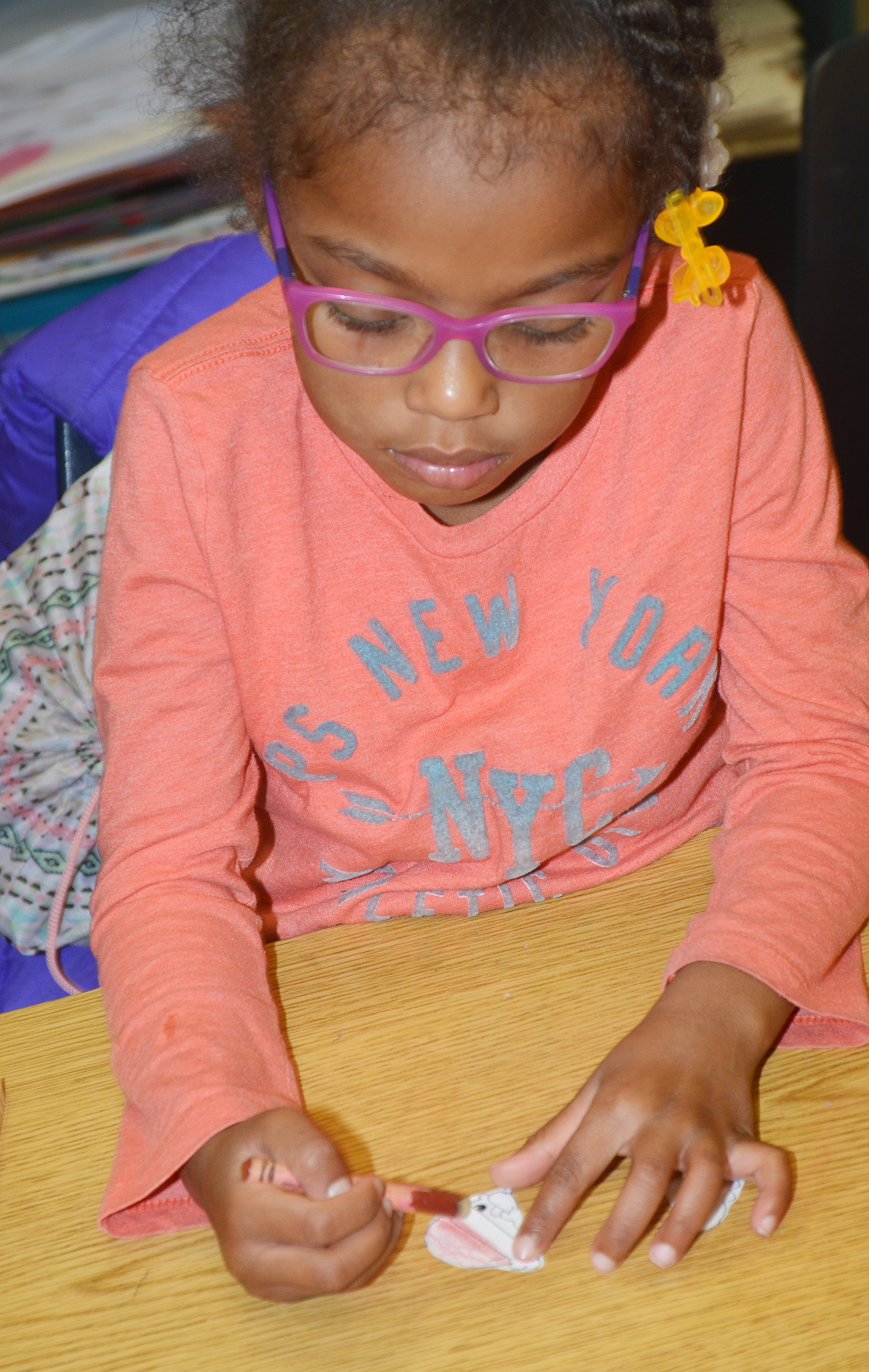 CES kindergartener Daya Griffin colors a picture of Santa, which she will glue on a clothespin.