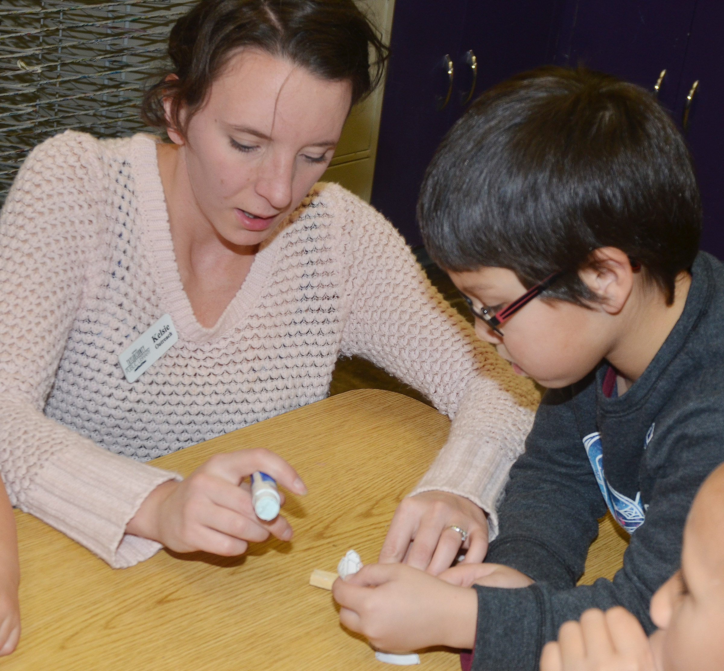 Kelsie Pepper from the Taylor County Public Library helps CES kindergartener Victrin Ramsey make his Santa clothespin.