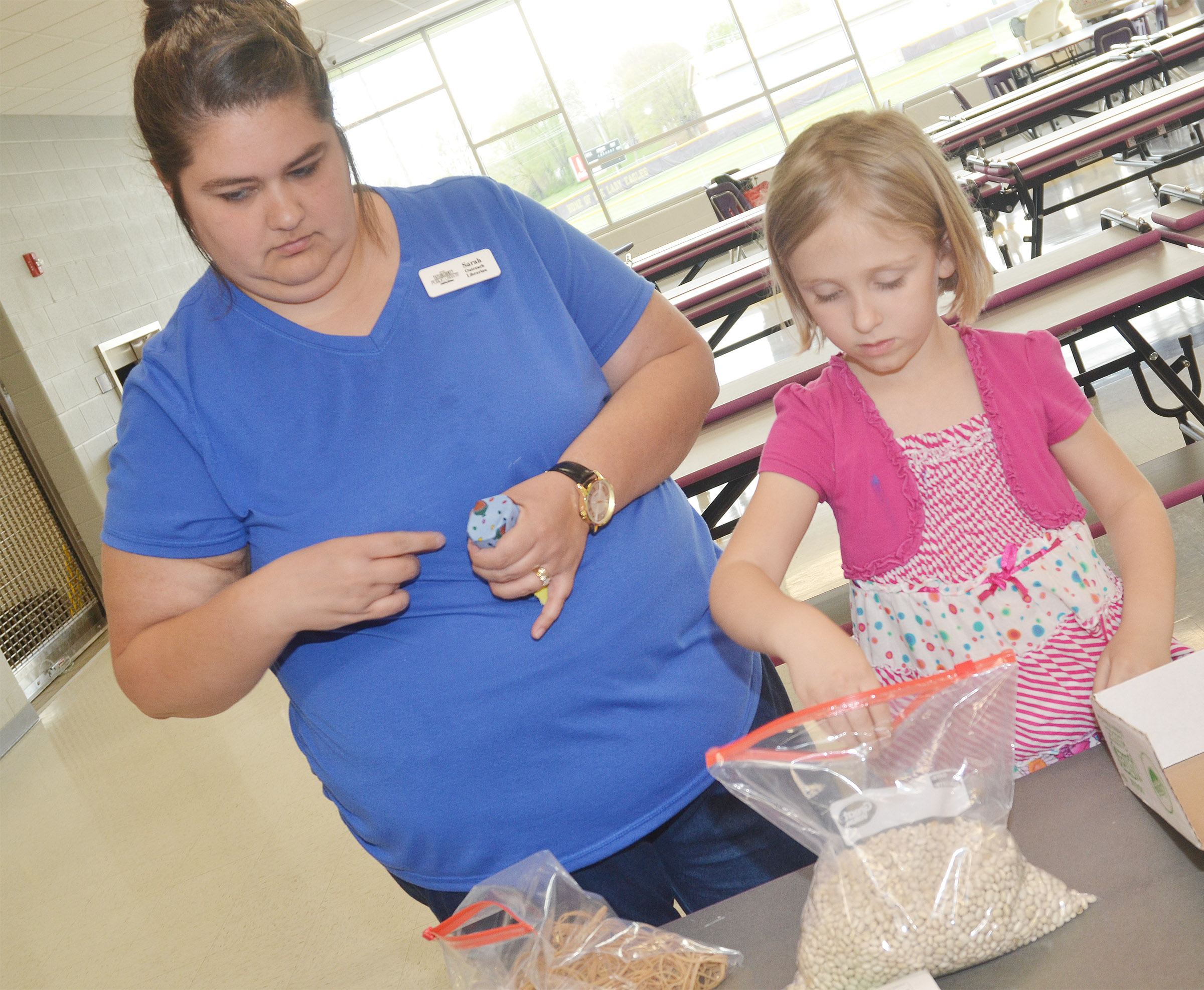 Sarah Hampton, Taylor County Public Library outreach librarian, helps CES kindergartener LeeAnna Garvin fill her maraca with beans.