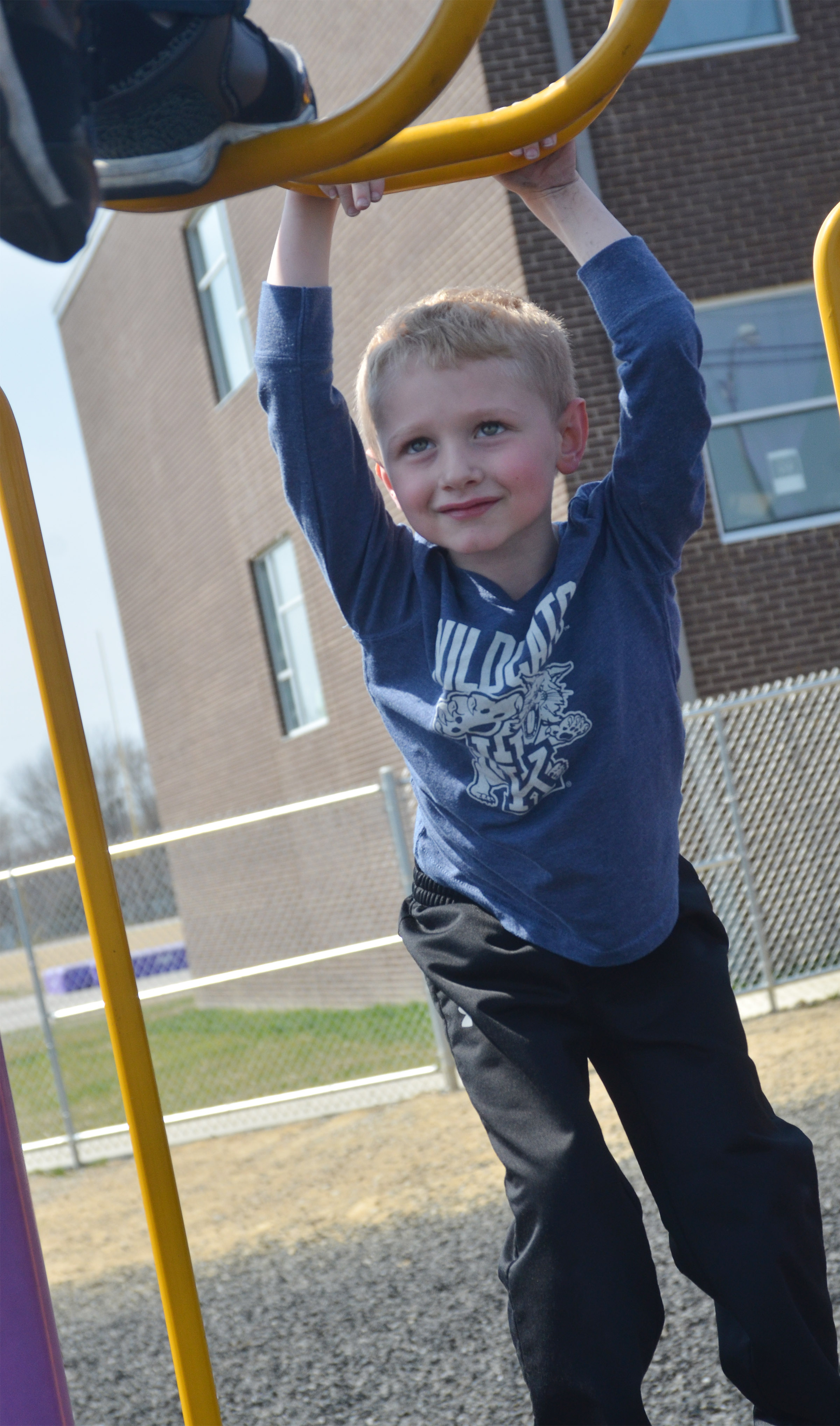 CES kindergartener Jackson Wright hangs on the monkey bars.