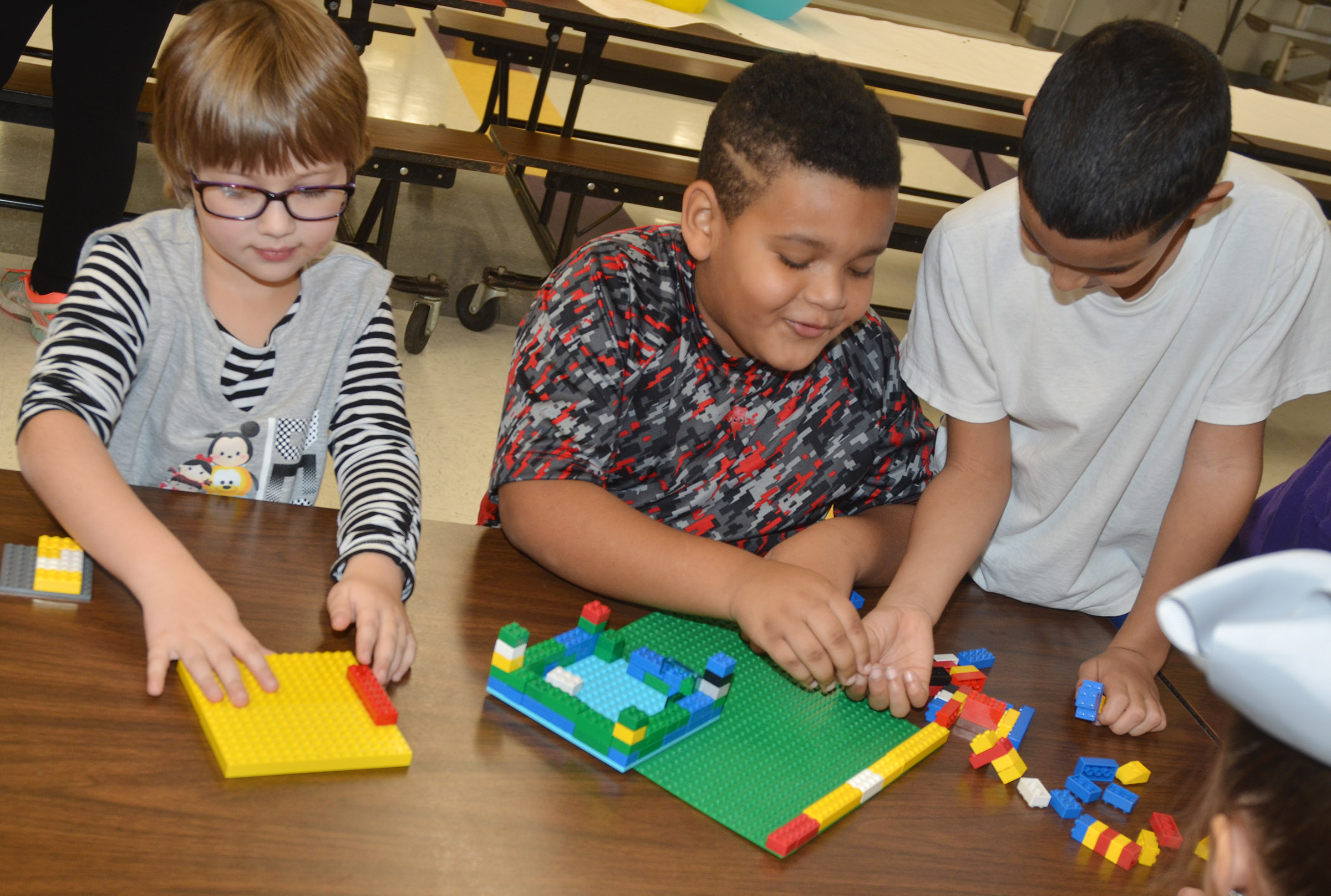 From left, CES first-grader Addelyn Dooley, second-grader Jayden Moore and first-grader Rizzo McKenzie build with Legos.