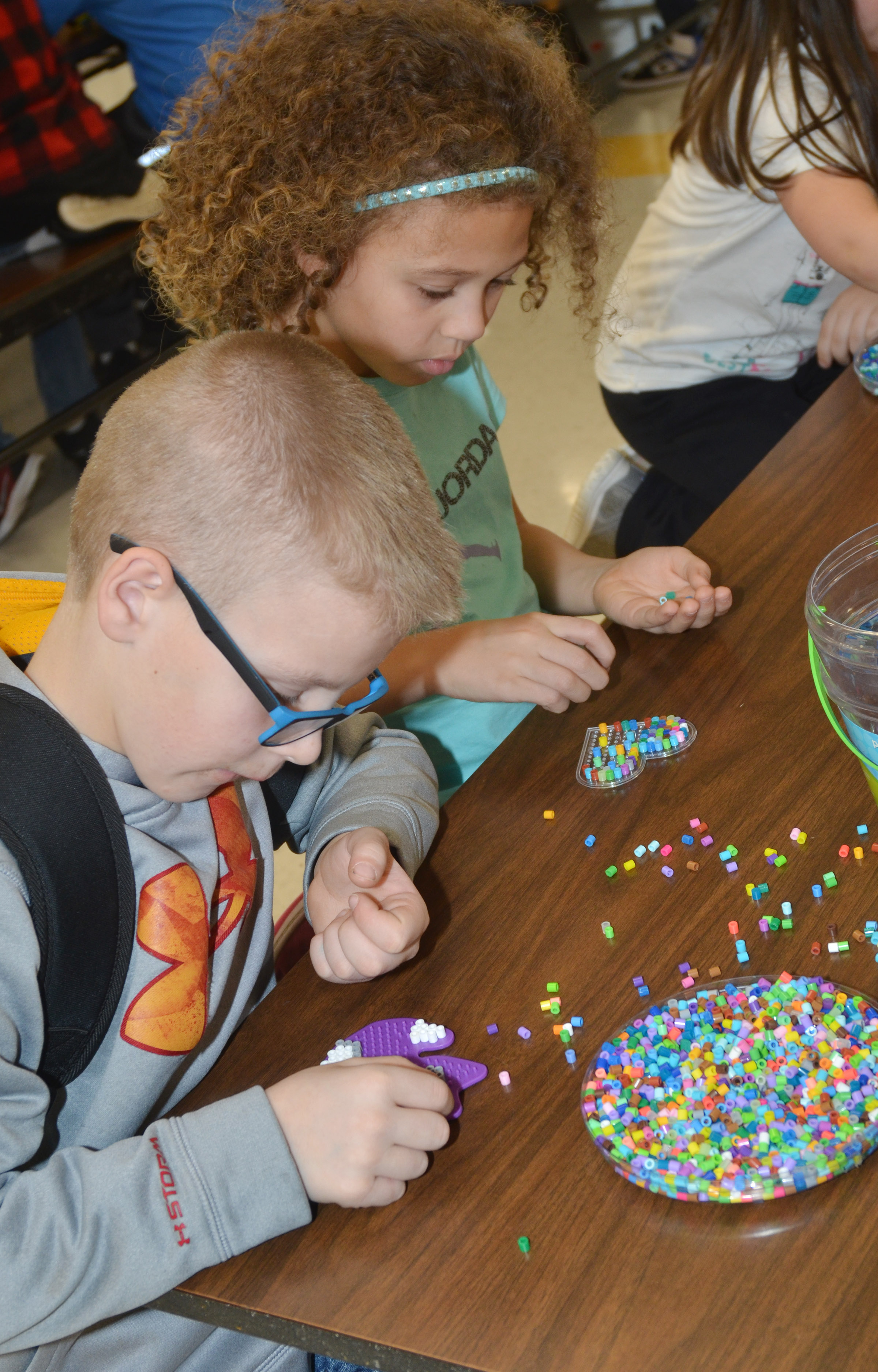 CES third-graders Ethan Irwin, at left, and Alicia Spaulding make designs with beads.