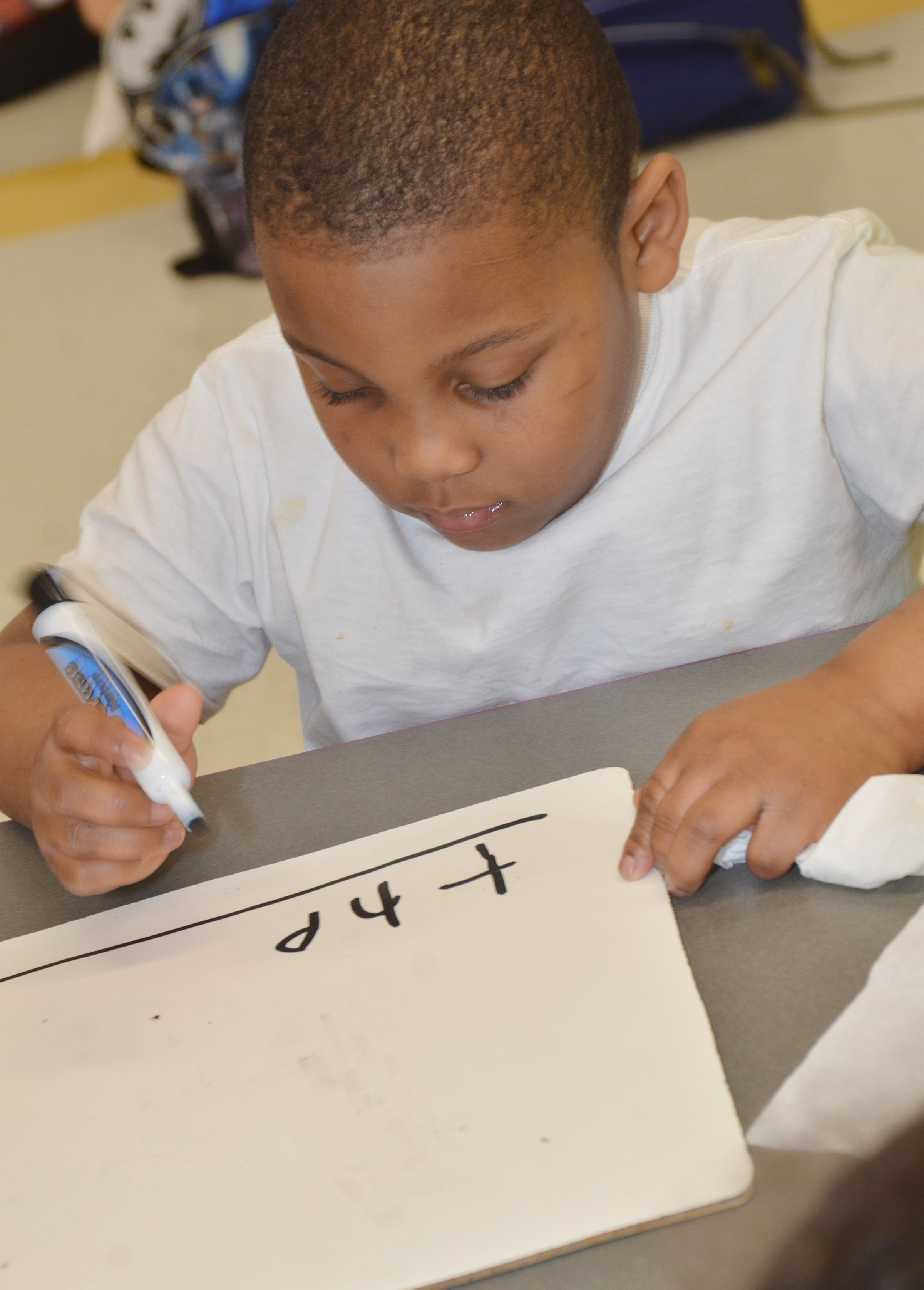 "CES kindergartener Malachi Conner writes the word ""the."""