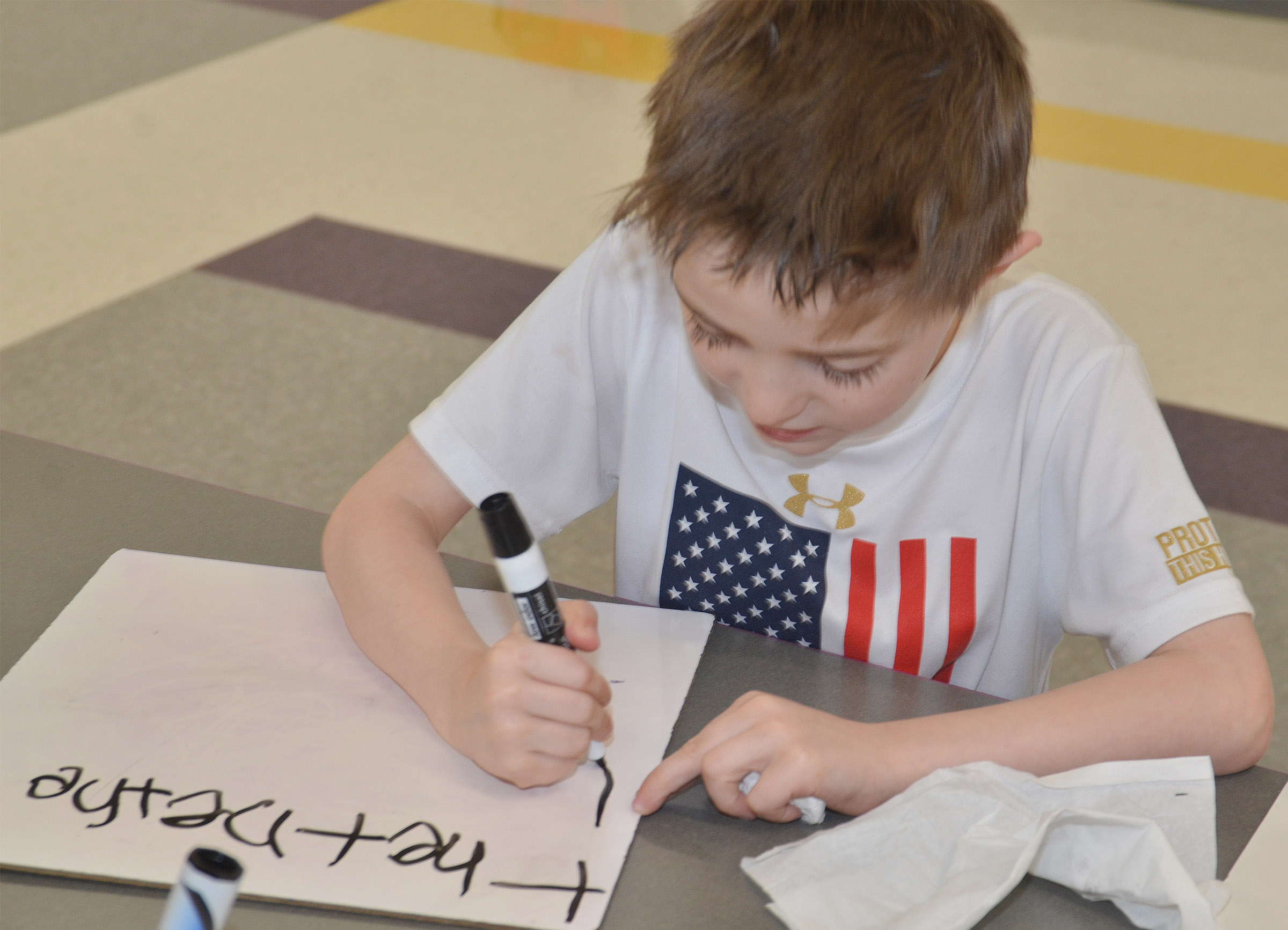 "CES kindergartener Caleb Goodson writes the word ""there."""