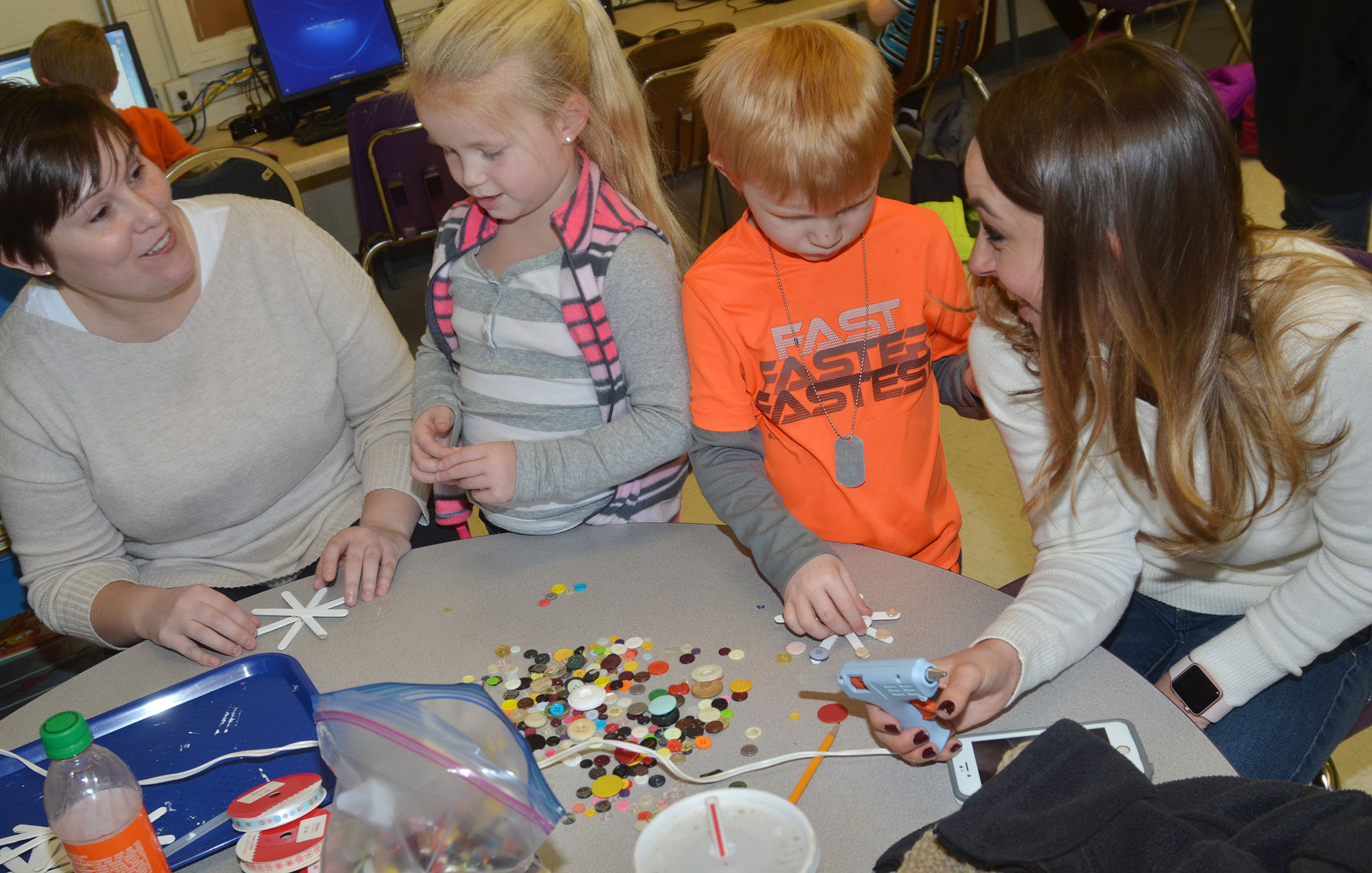 CES Wings Express Director Amanda Barnett, at left, and Campbellsville University education student Abi Dean help kindergarteners Lillie Judd and Jayden Maupin glue buttons on their snowflakes.