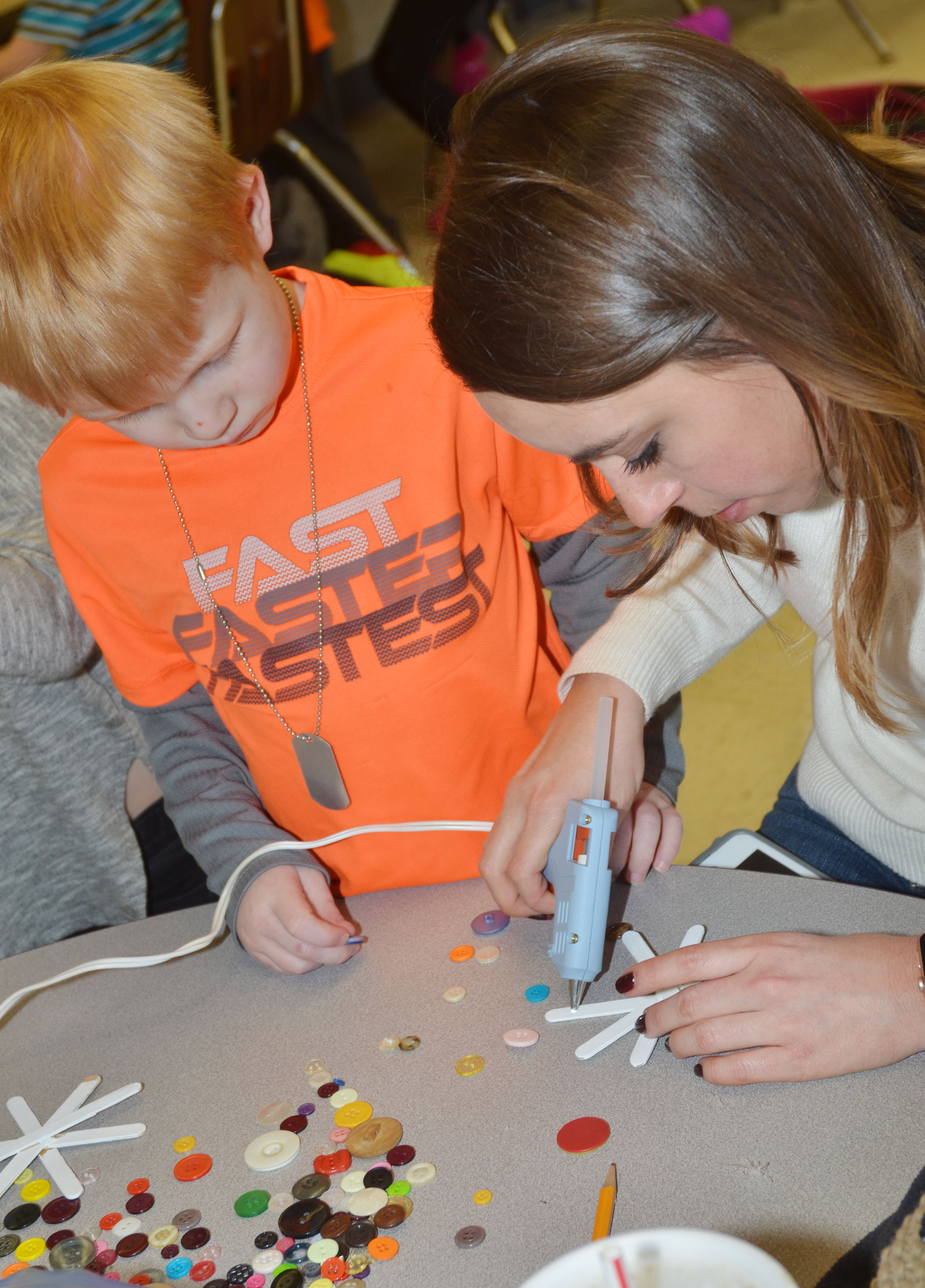 Campbellsville University education student Abi Dean helps CES kindergartener Jayden Maupin glue buttons on his snowflake.
