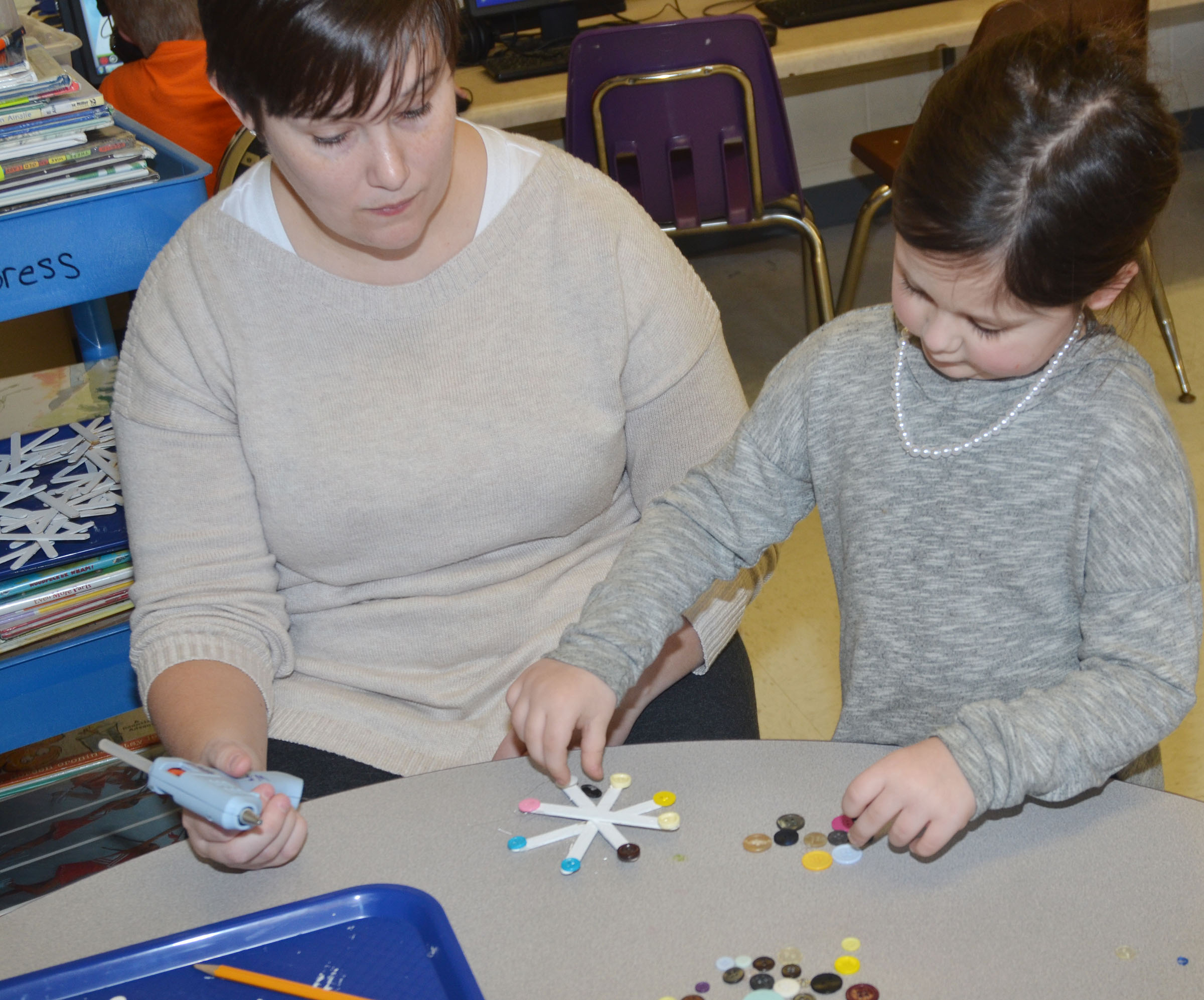 CES Wings Express Director Amanda Barnett helps CES kindergartener Trinity Clark glue buttons on her snowflake.