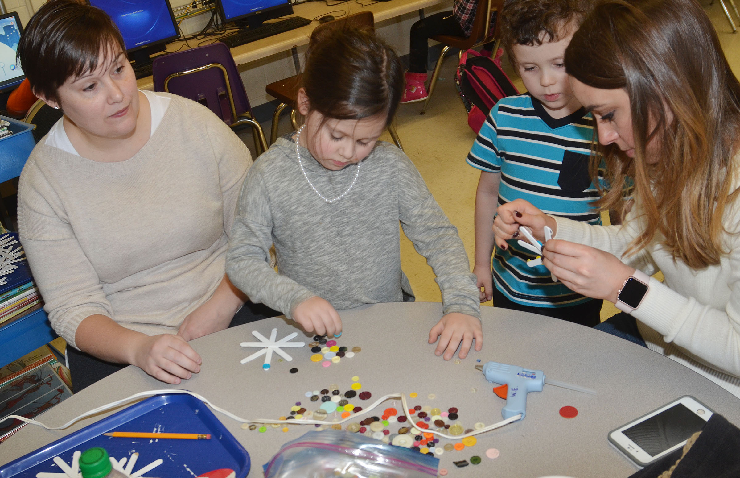 CES Wings Express Director Amanda Barnett, at left, and Campbellsville University education student Abi Dean help kindergarteners Trinity Clark and Braydan Dyer add buttons to their snowflakes.
