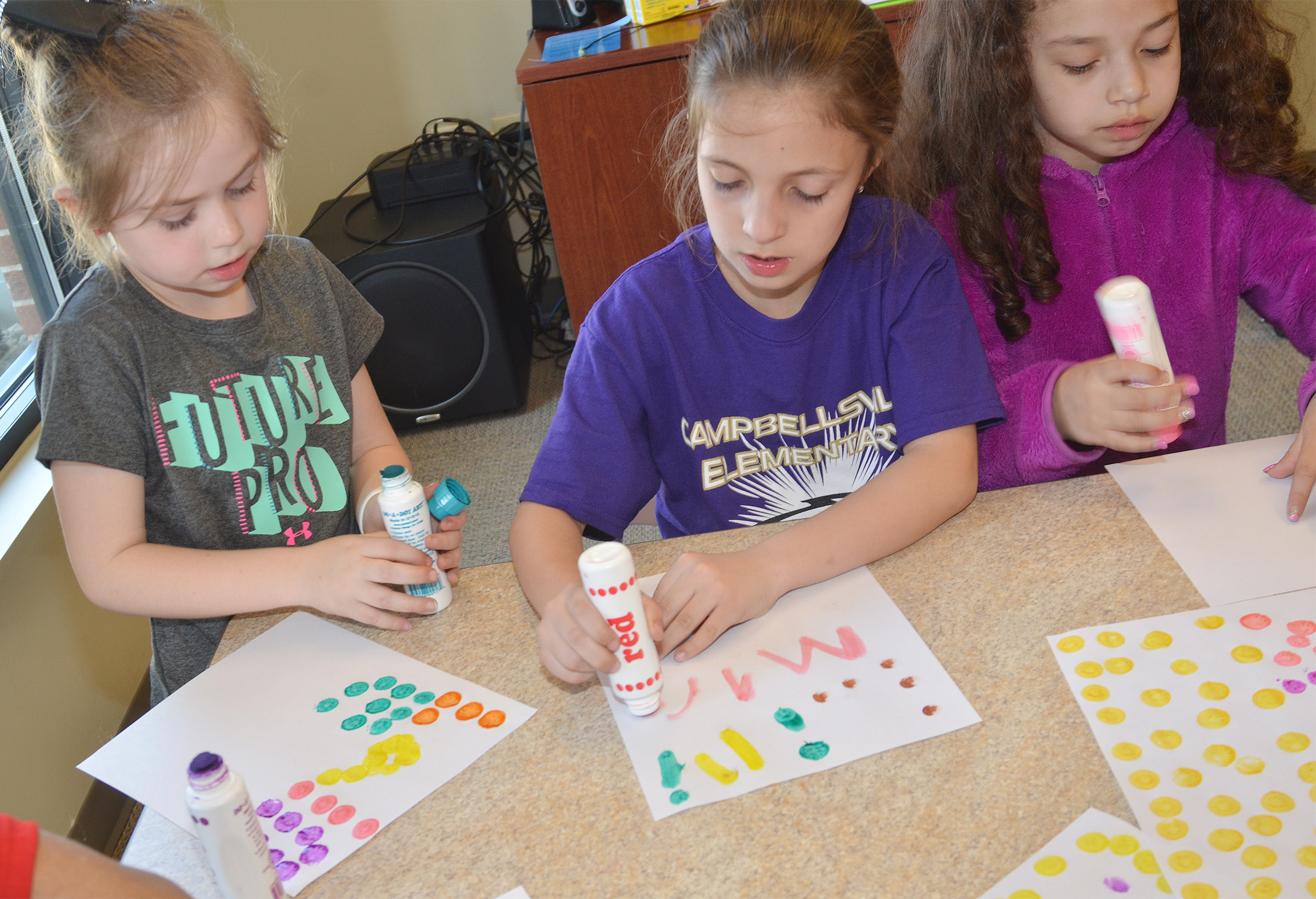 From left, CES first-graders Lainey Price, Lillian Martin and Ammarissa Nunez paint at the library.