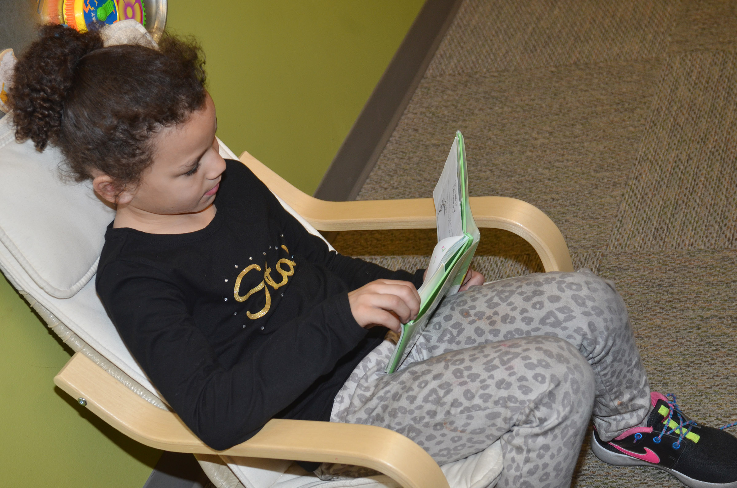 CES kindergartener Aleeya Spaulding reads at the library.