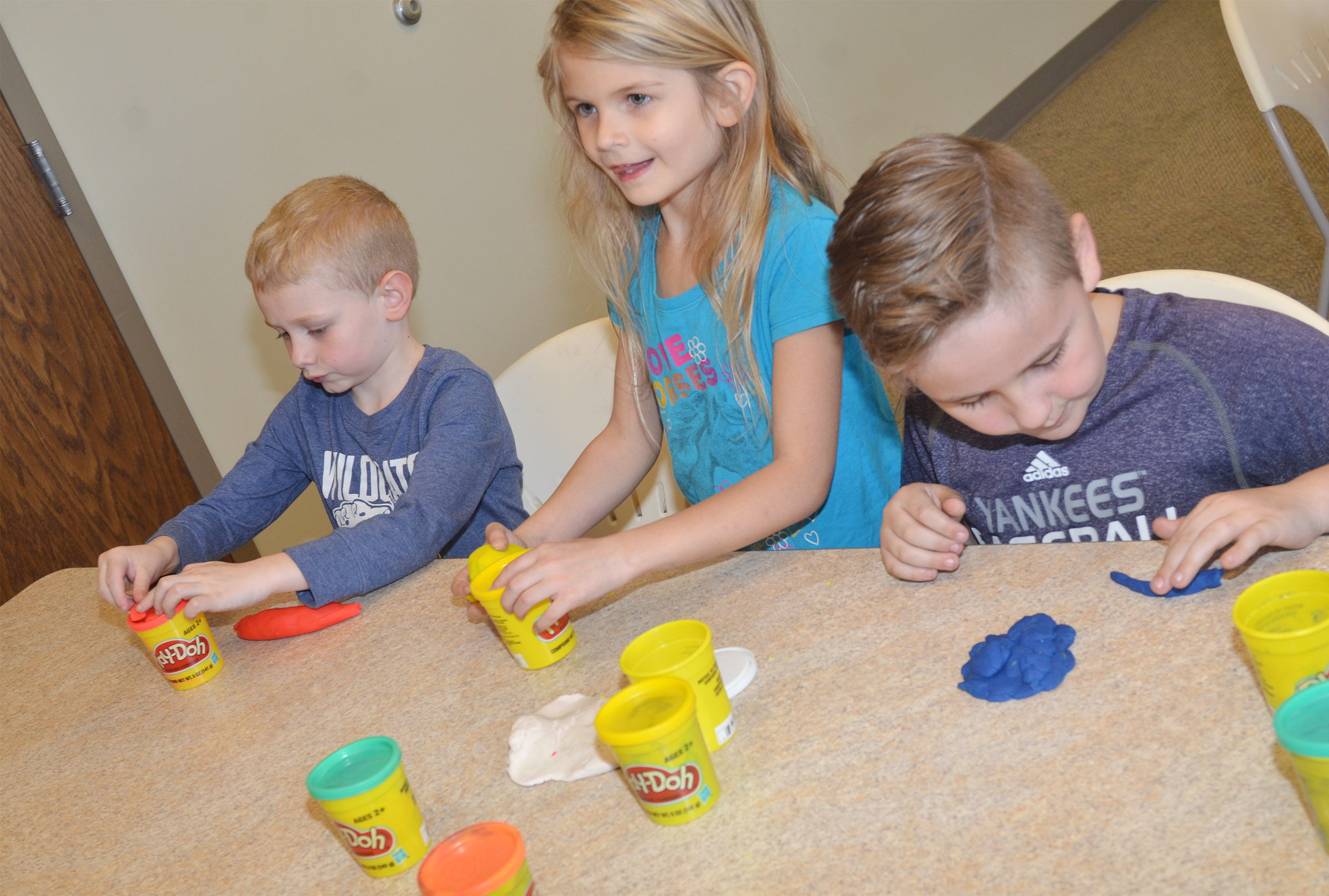 From left, CES kindergarteners Jackson Wright, Gracie Gebler and Braxton Rhodes play with Play-Doh at the library.