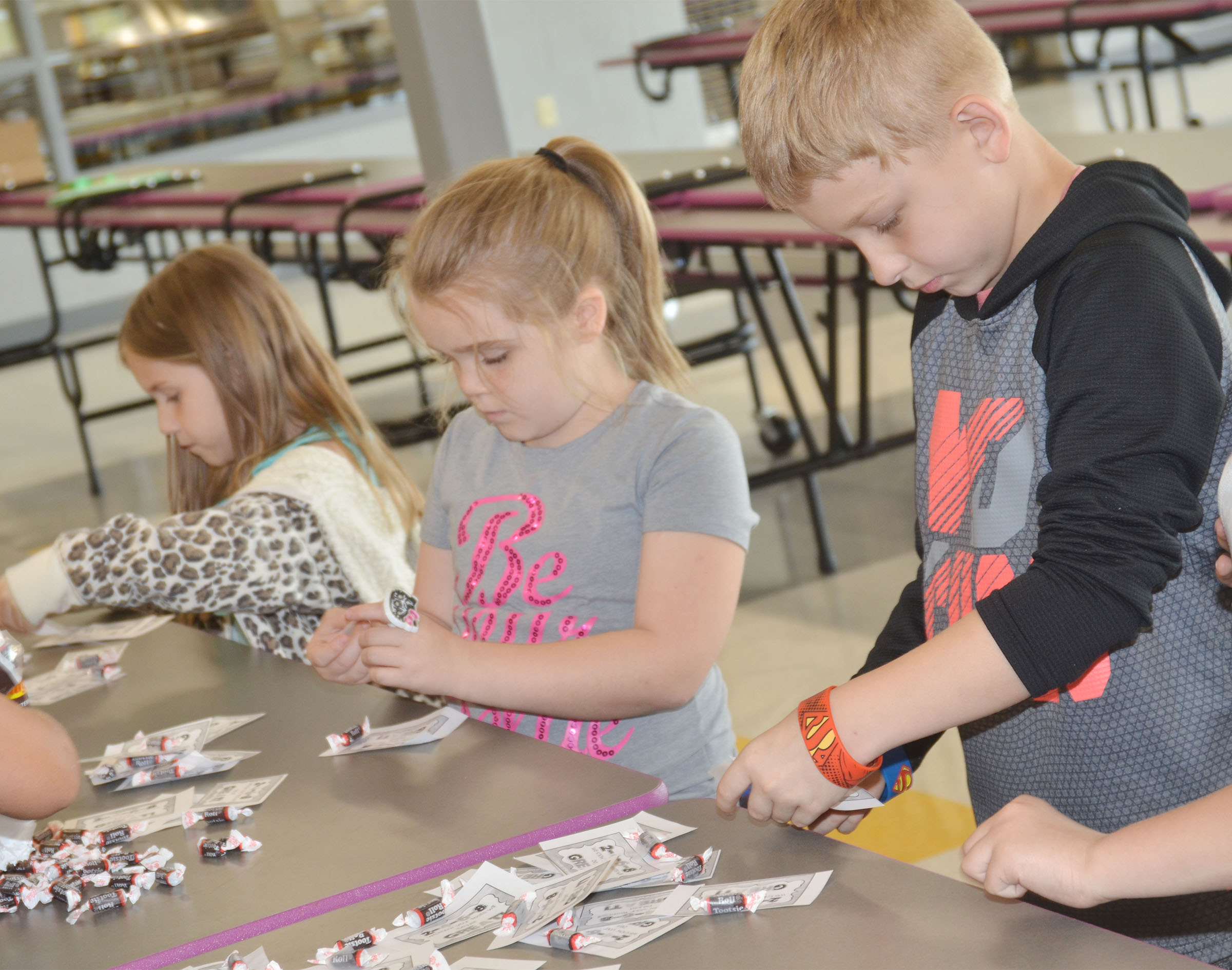 CES second-graders Jaylin Christie, at left, and Mason Davis sort Tootsie Rolls for third-graders.